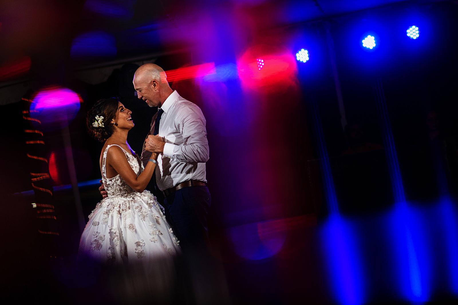 Primer baile como marido y mujer en el día de su boda en la playa, através de luces de colores