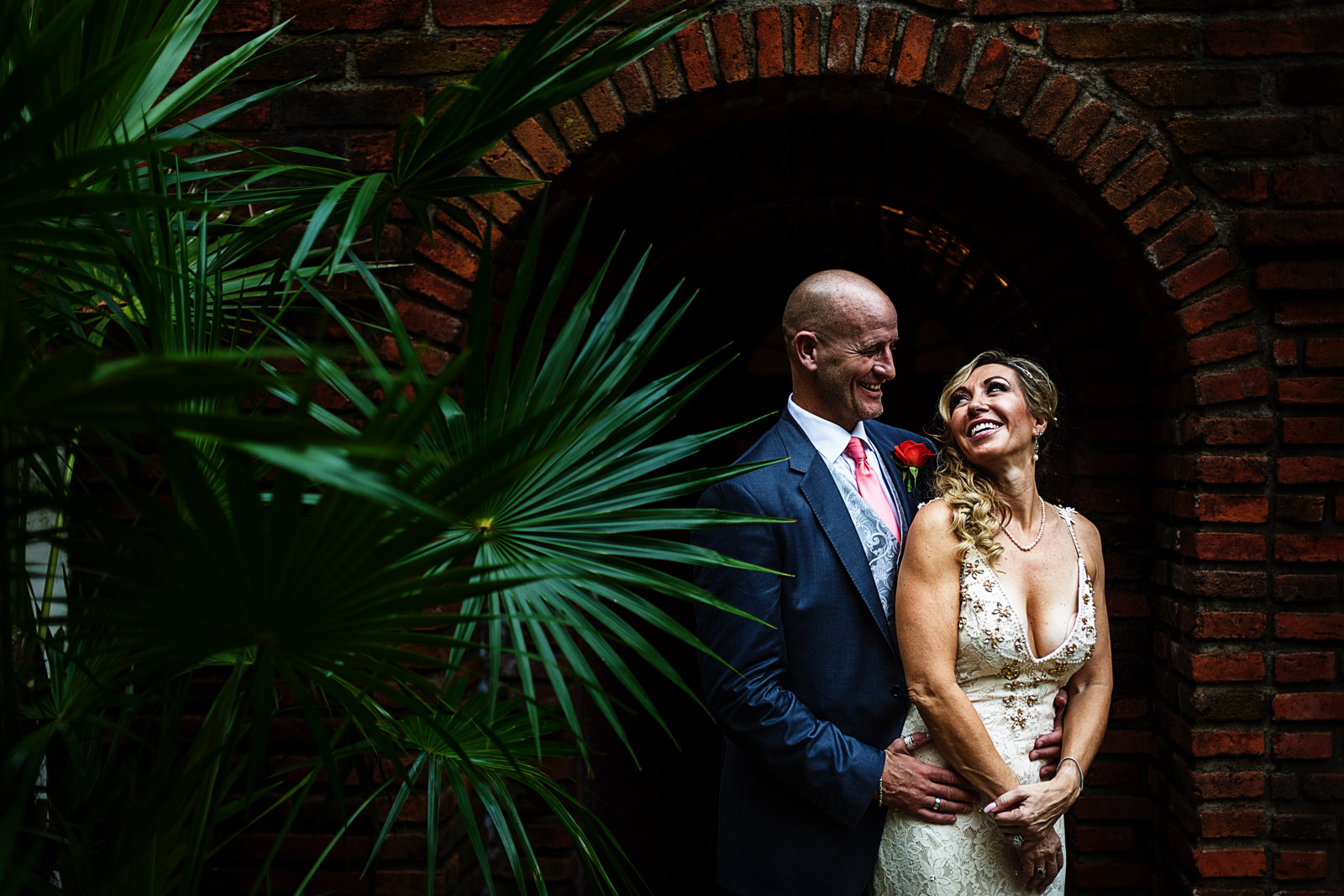 Bride and groom standing at the beginning of a tunnel next to a palm plant