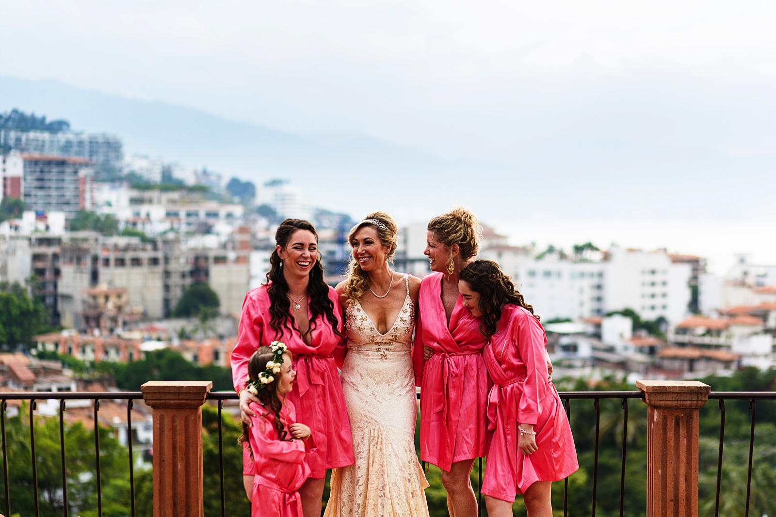 Bride and bridesmaids stand at the terrace of the bridal suite at Hacienda San Angel with an amazing view of Puerto Vallarta in the background