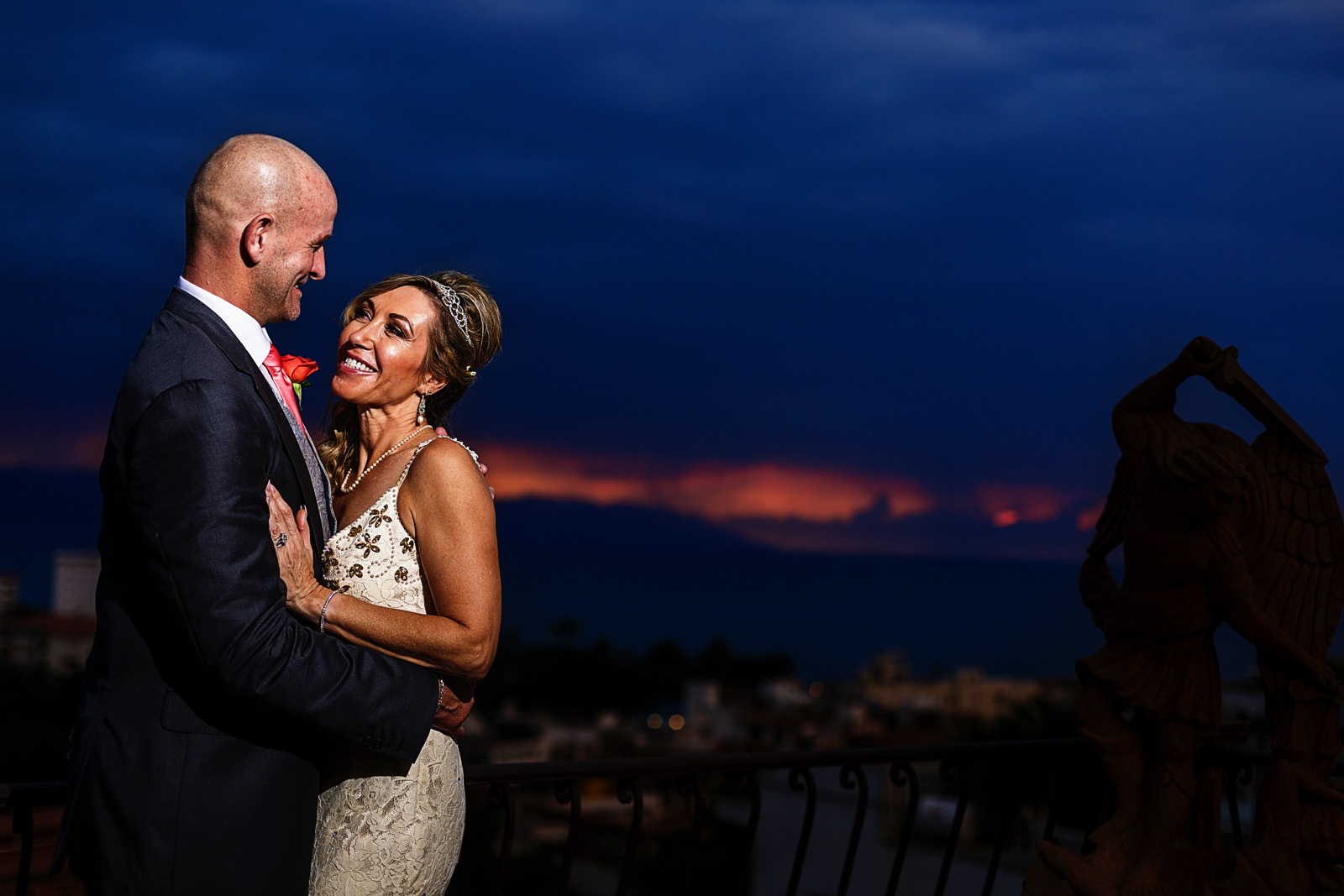 Wedding couple's portrait at the terrace of the bridal suite with a view of Puerto Vallarta in the sunset