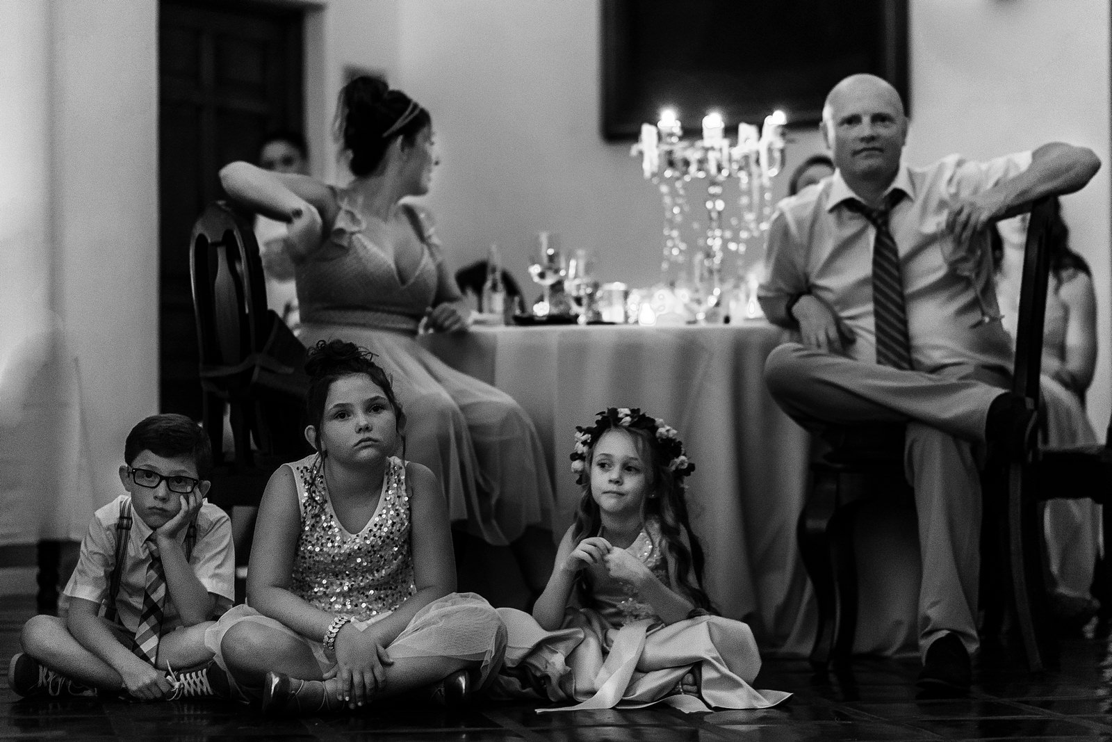 Different reactions from adults sitting on chairs and kids sitting on the floor at the wedding reception in Hacienda San Angel Puerto Vallarta
