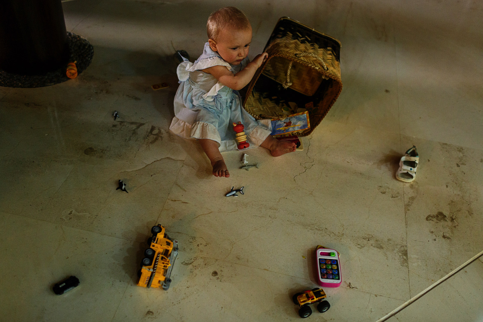 Baby girl making a mess with the basket of toys