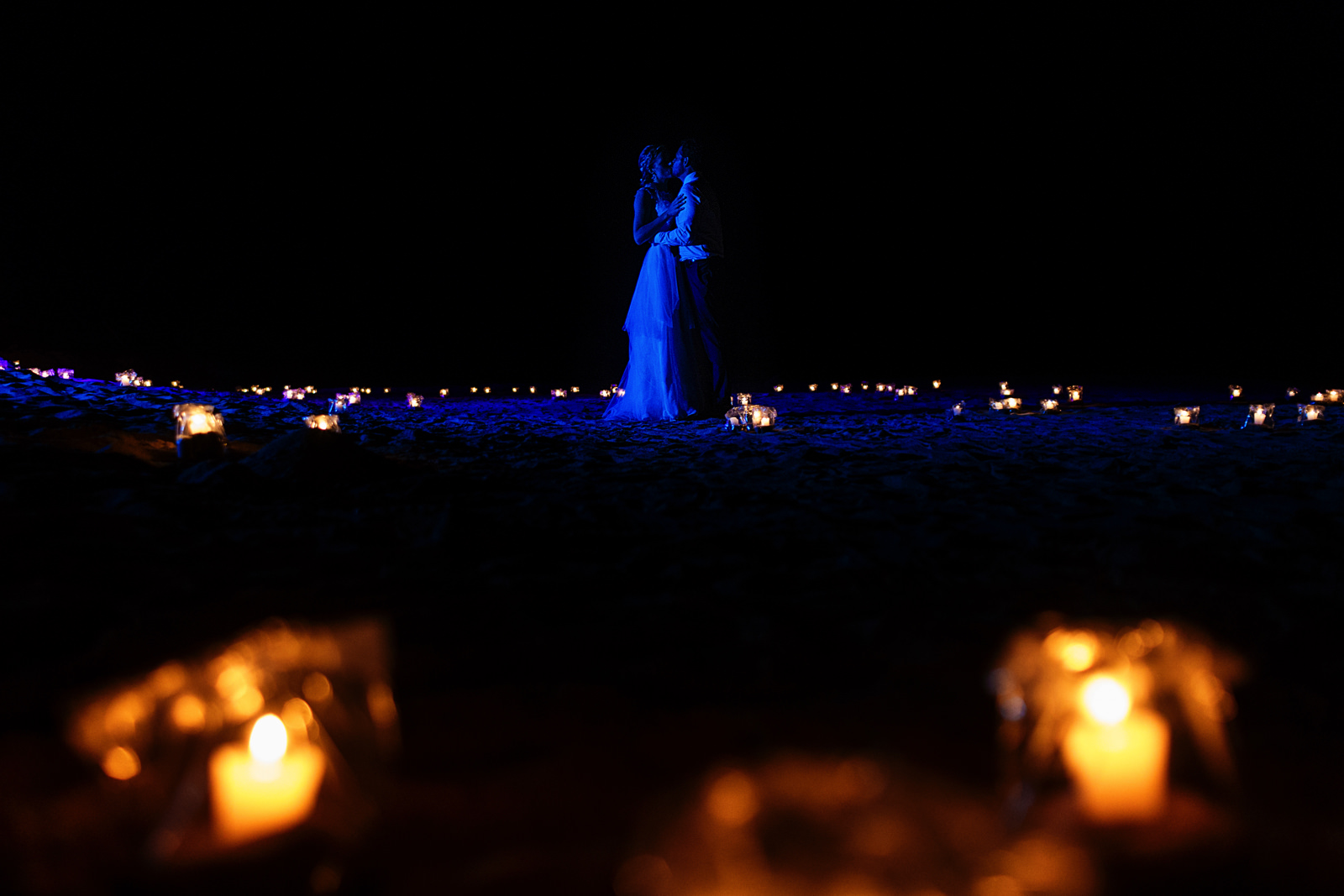 Bride and groom kiss under the blue light against dozens of candle lights