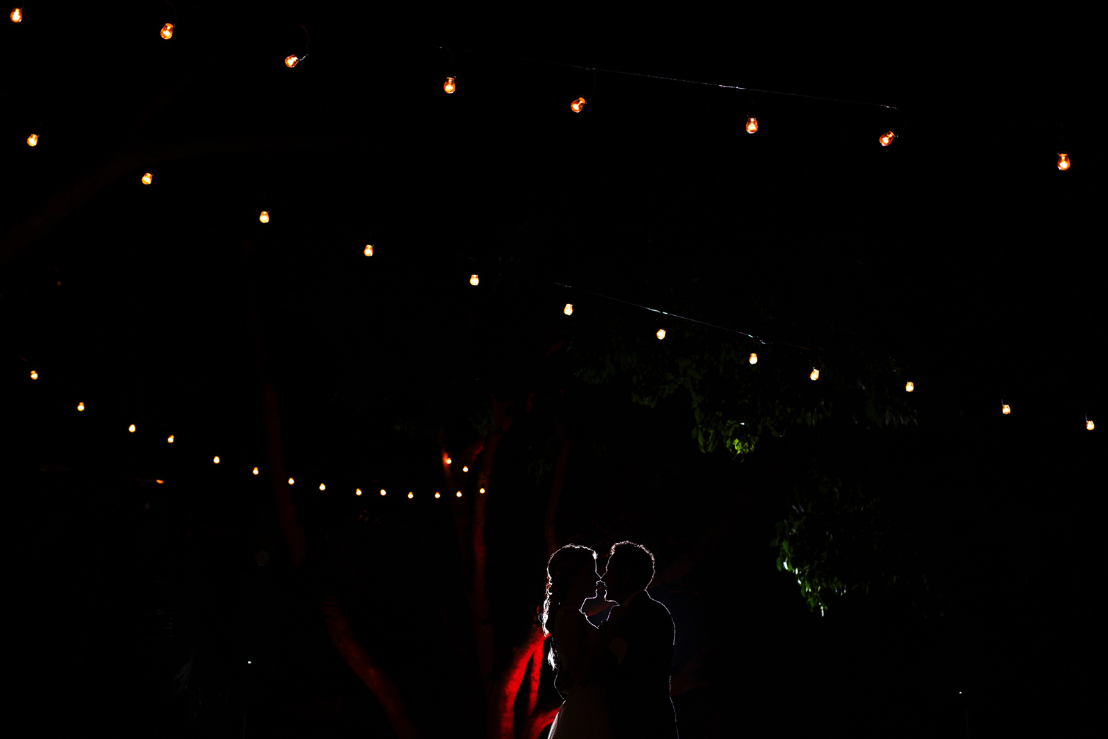 Silhouettes of groom and bride during their first dance with hanging light bulbs