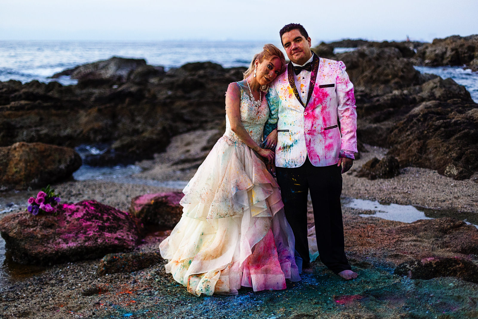 Groom and bride standing side by side near the pacific ocean and covered in colorful holi powder