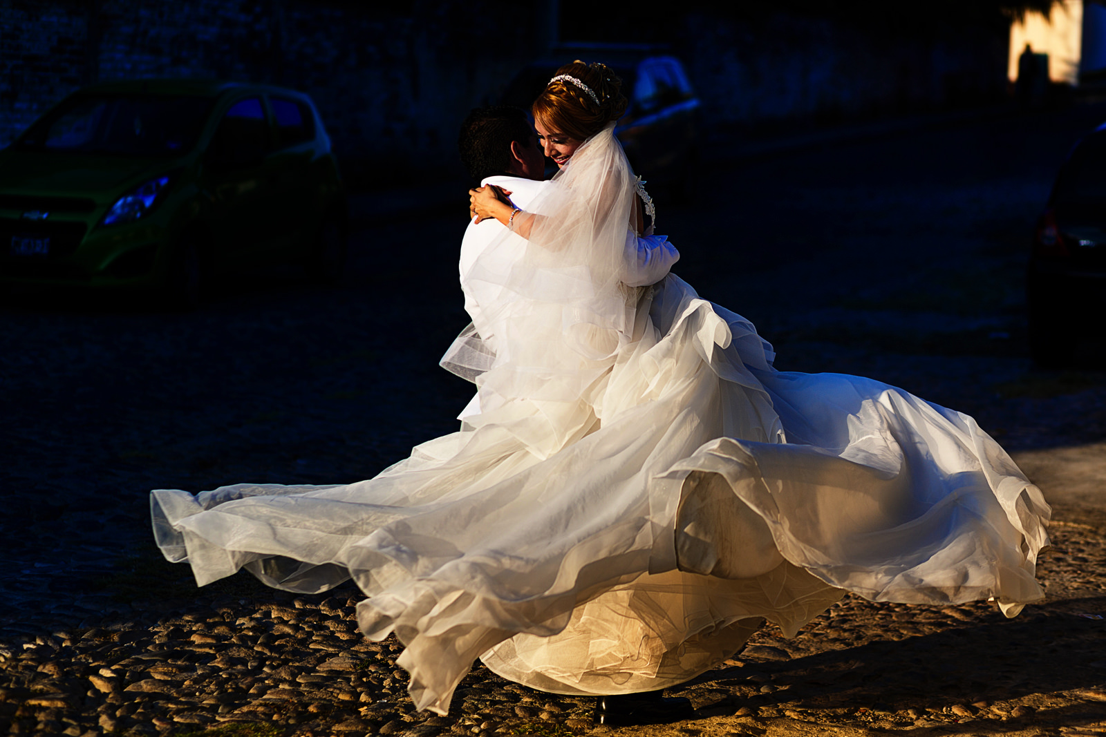Groom spinning the bride and the dress flowing as they turn on the shinny sun light in the streets of Bucerias