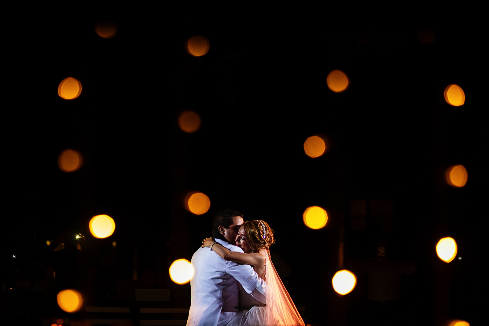 Bride and groom on their first dance thru tiny bulb lights