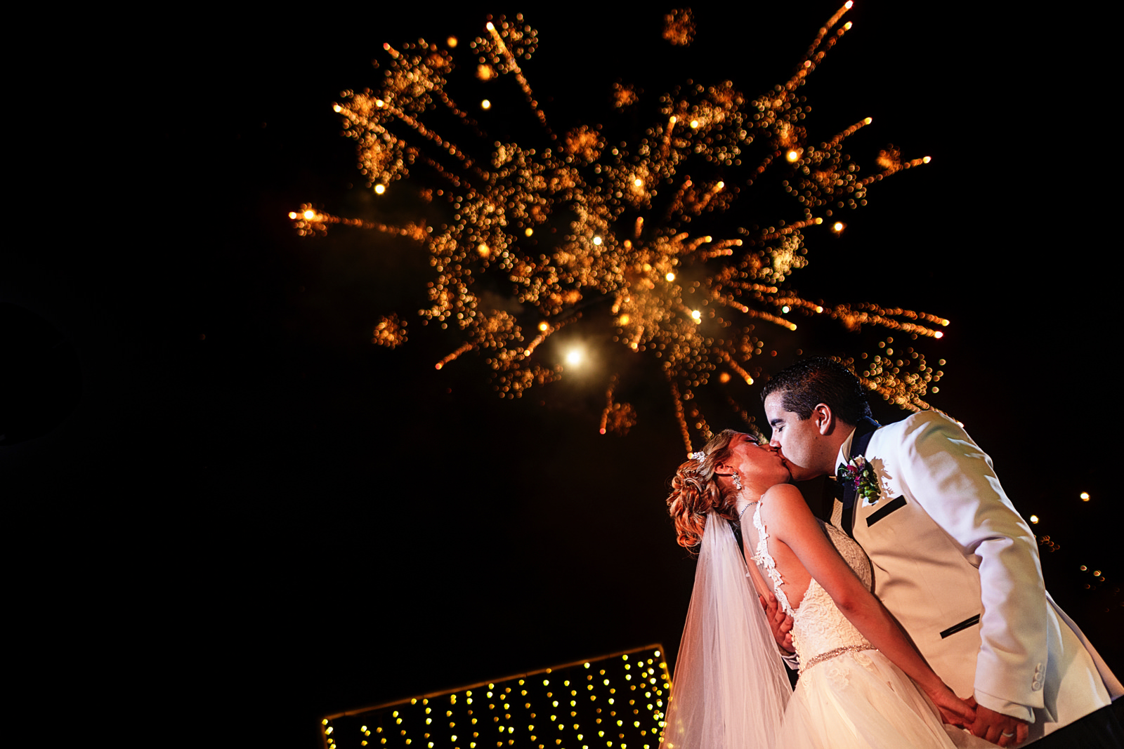 Bride and groom kiss under the fireworks at the end of their first dance as married couple