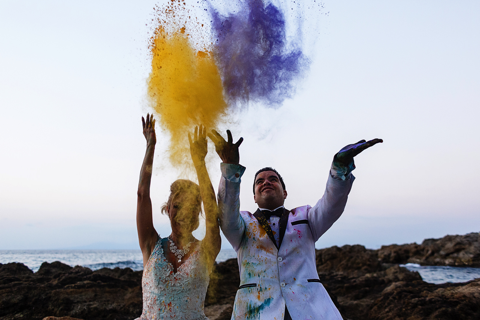Groom and bride throw colorful holy powder above them