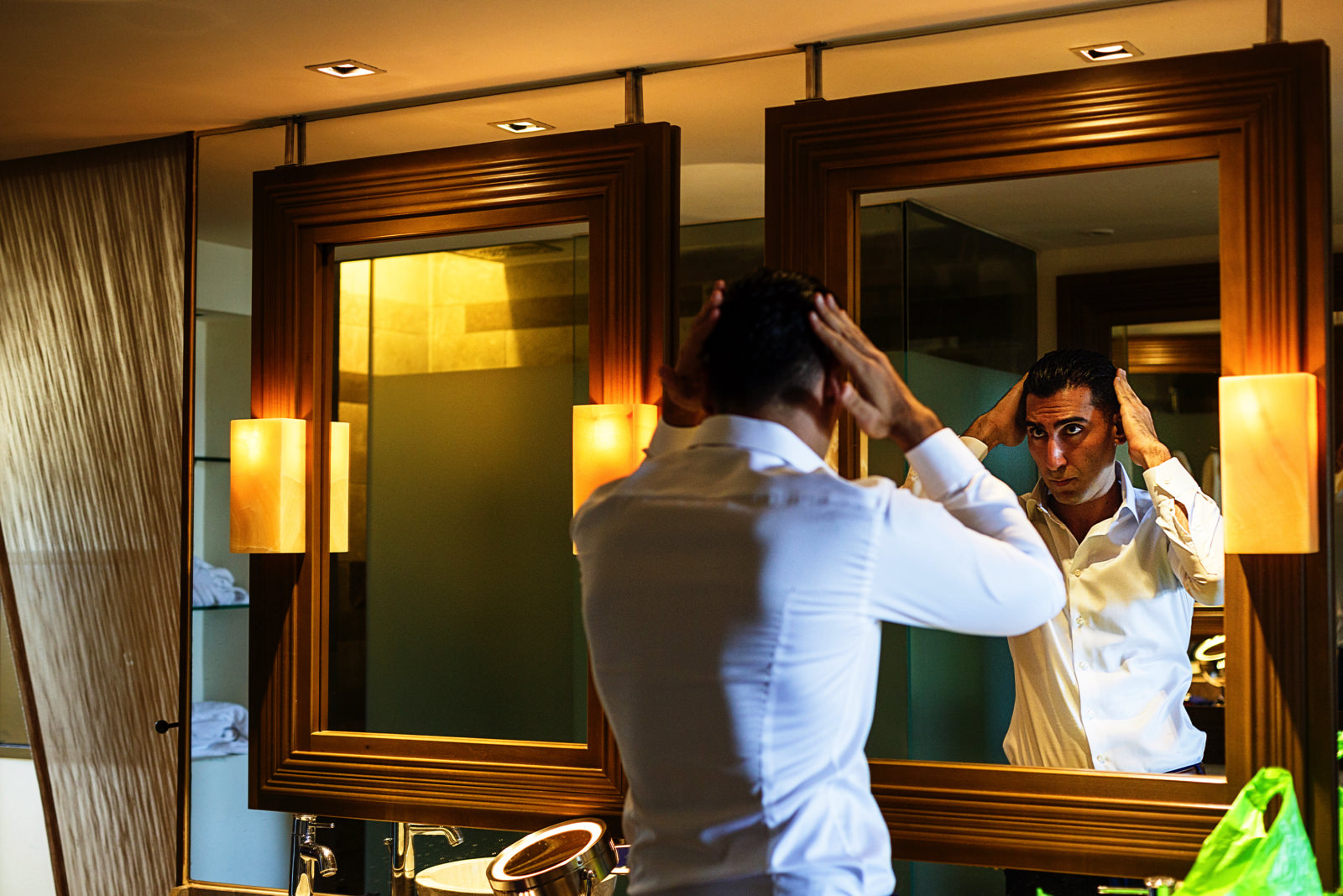 Groom in front of the mirror doing his hair at the Now Amber resort room