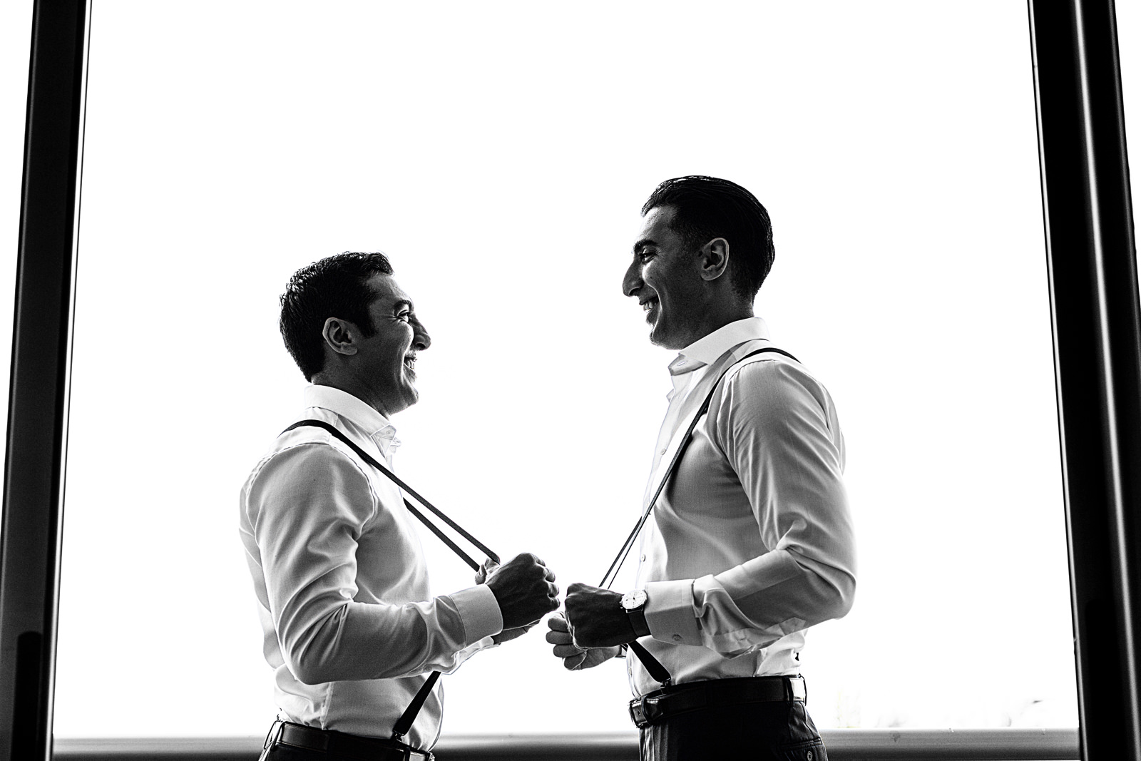 Groom and bestman holding the suspenders for a portrait
