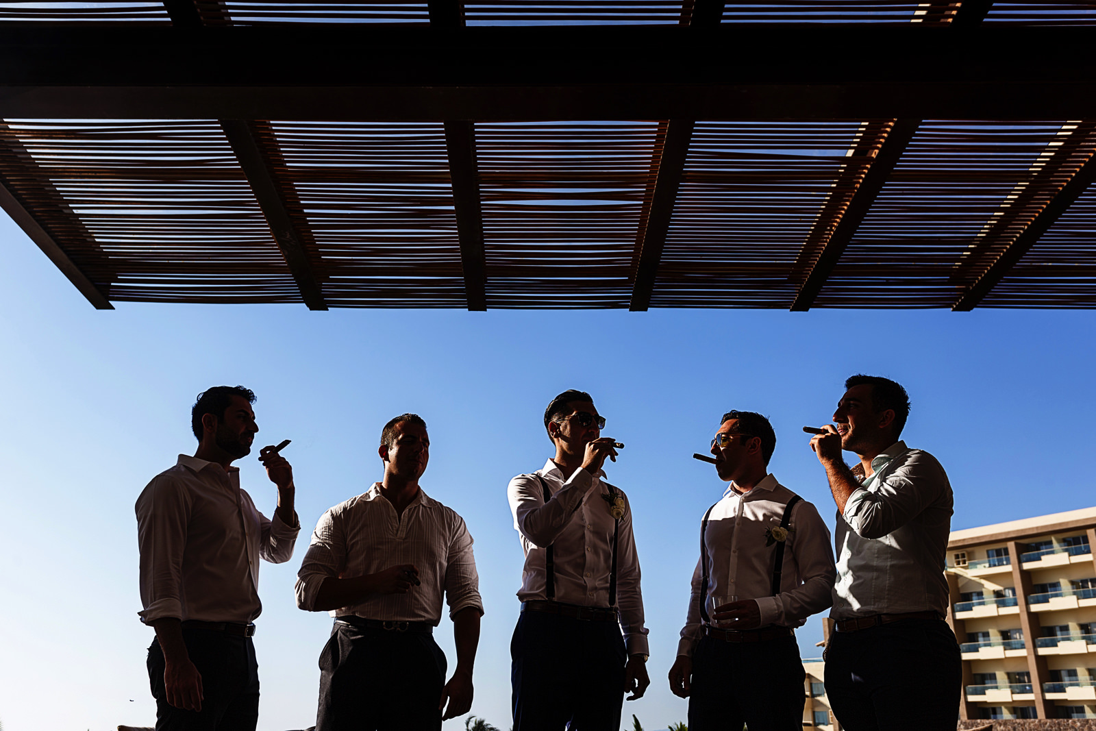 Groom and groomsmen smoking cigars at the Now Amber lobby