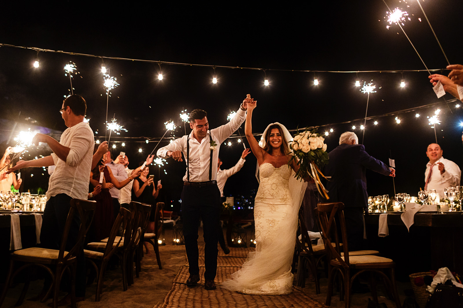 Bride and groom entrance into the reception with friends and family holding sparklers around them