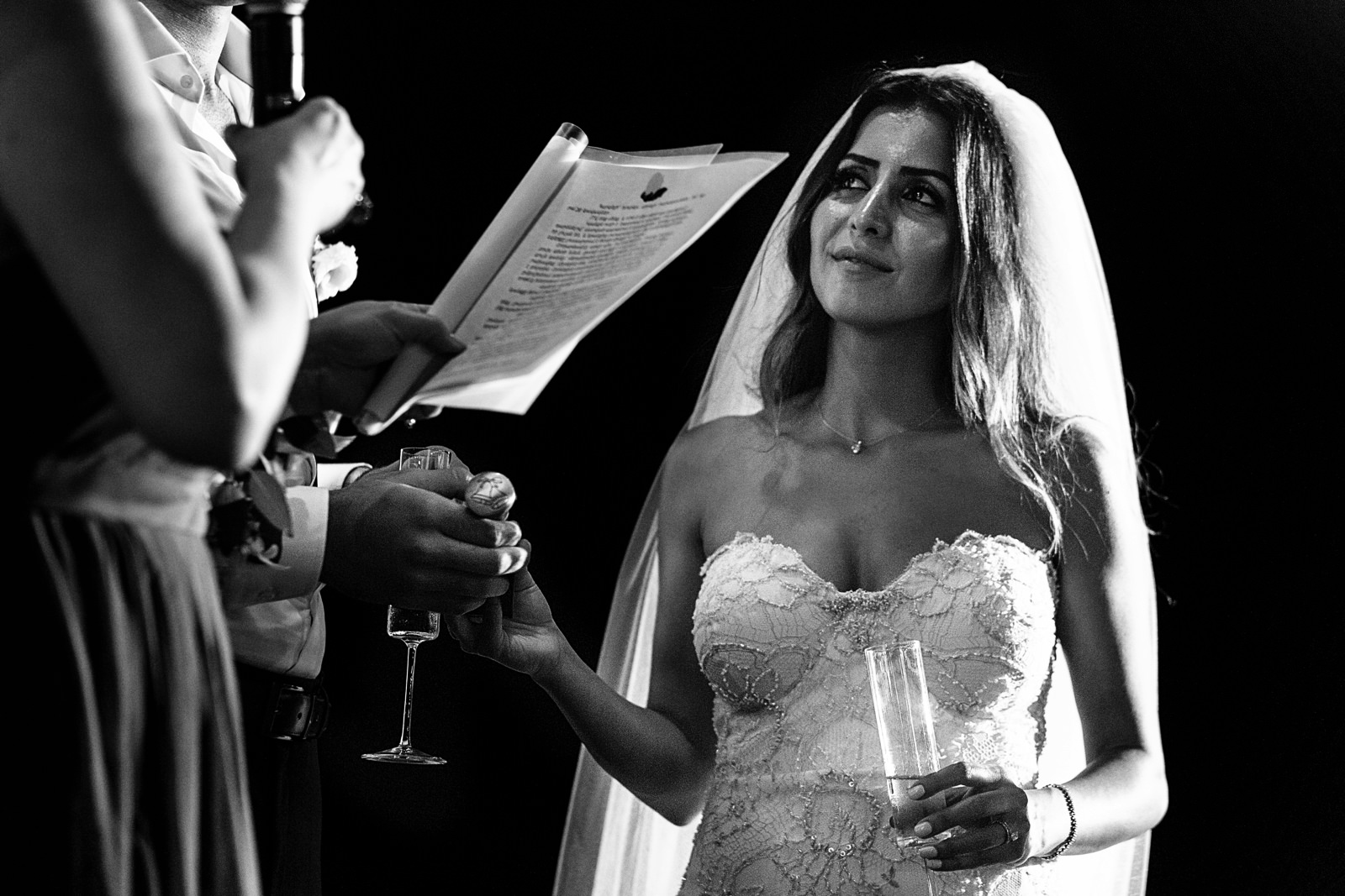 Bride looking at her mom during a speech while the groom holds her hand