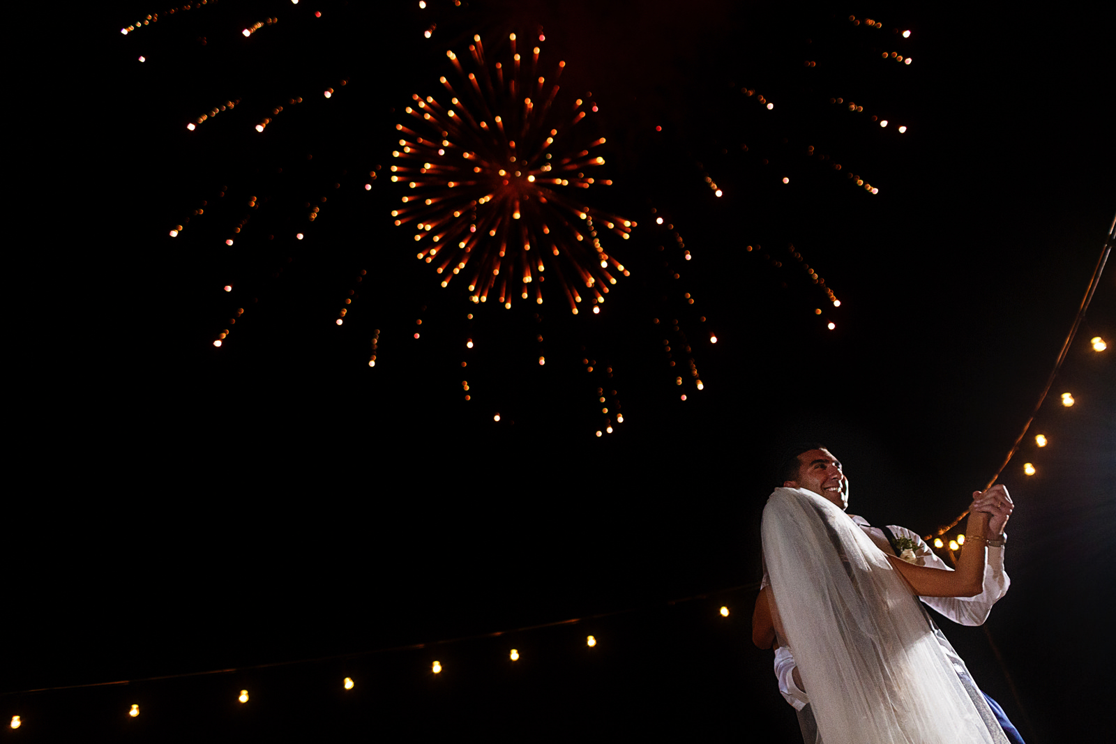 Fireworks explodng above the groom and bride on their first dance