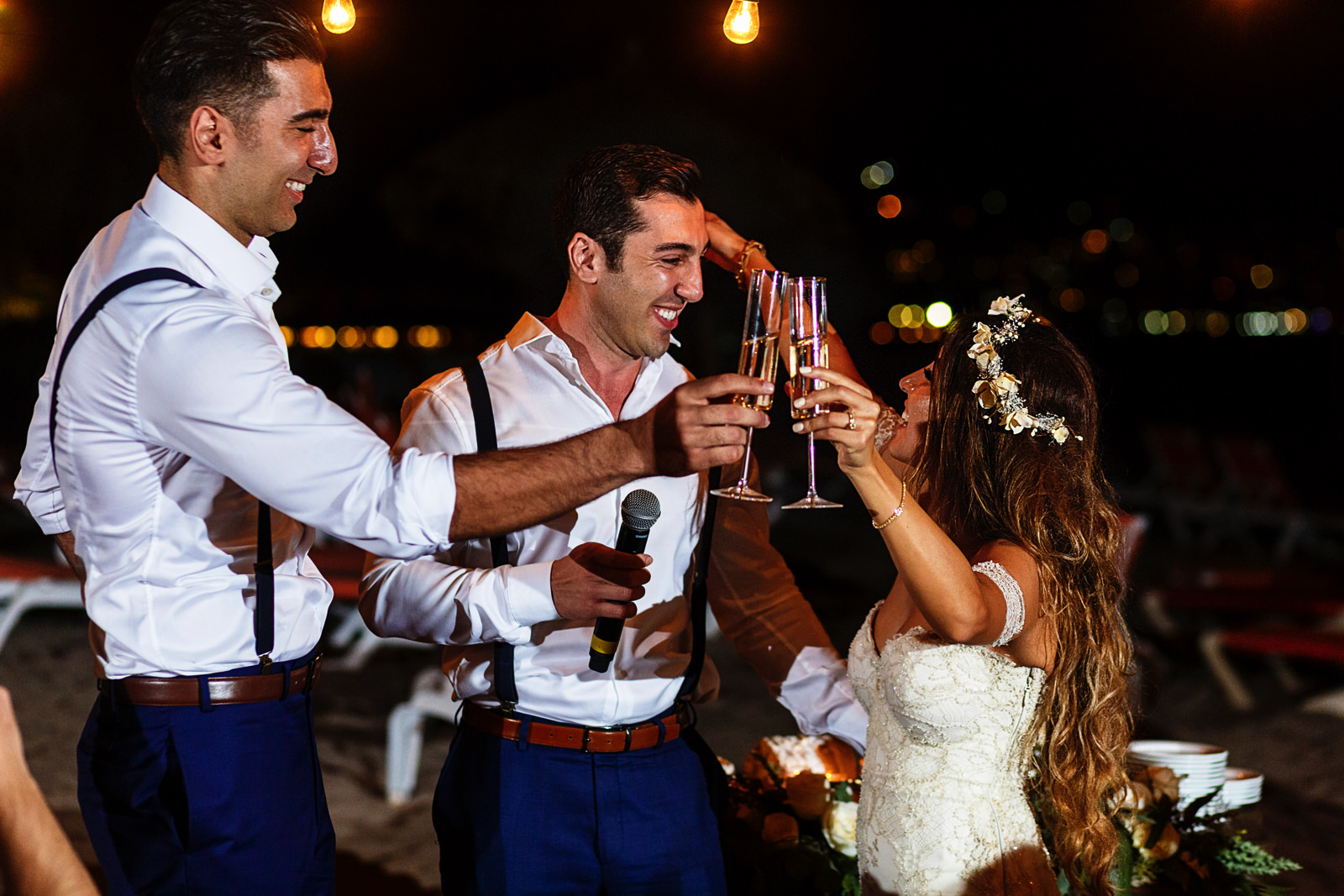 Bride about to hug the best-man and cling her champagne glass with the groom after the speech