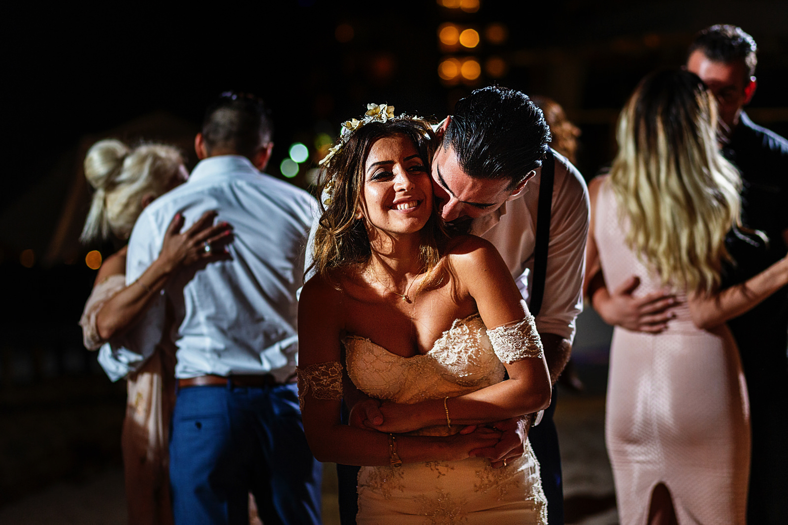 Groom hugs bride from behind in the middle of the dance floor