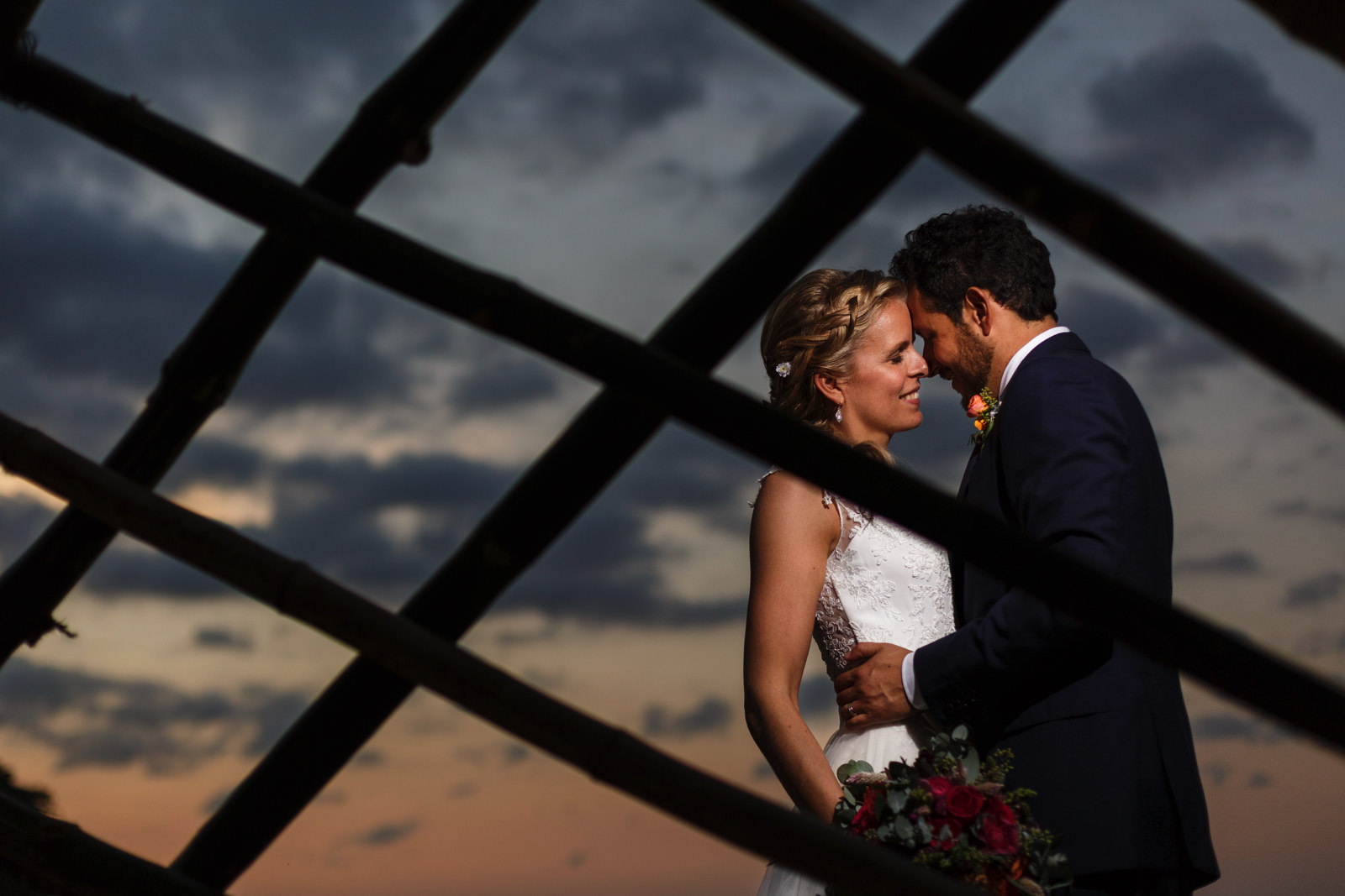 Silhouette of the groom and bamboo grid while bride stands under the light during sunset in the Mexican pacific
