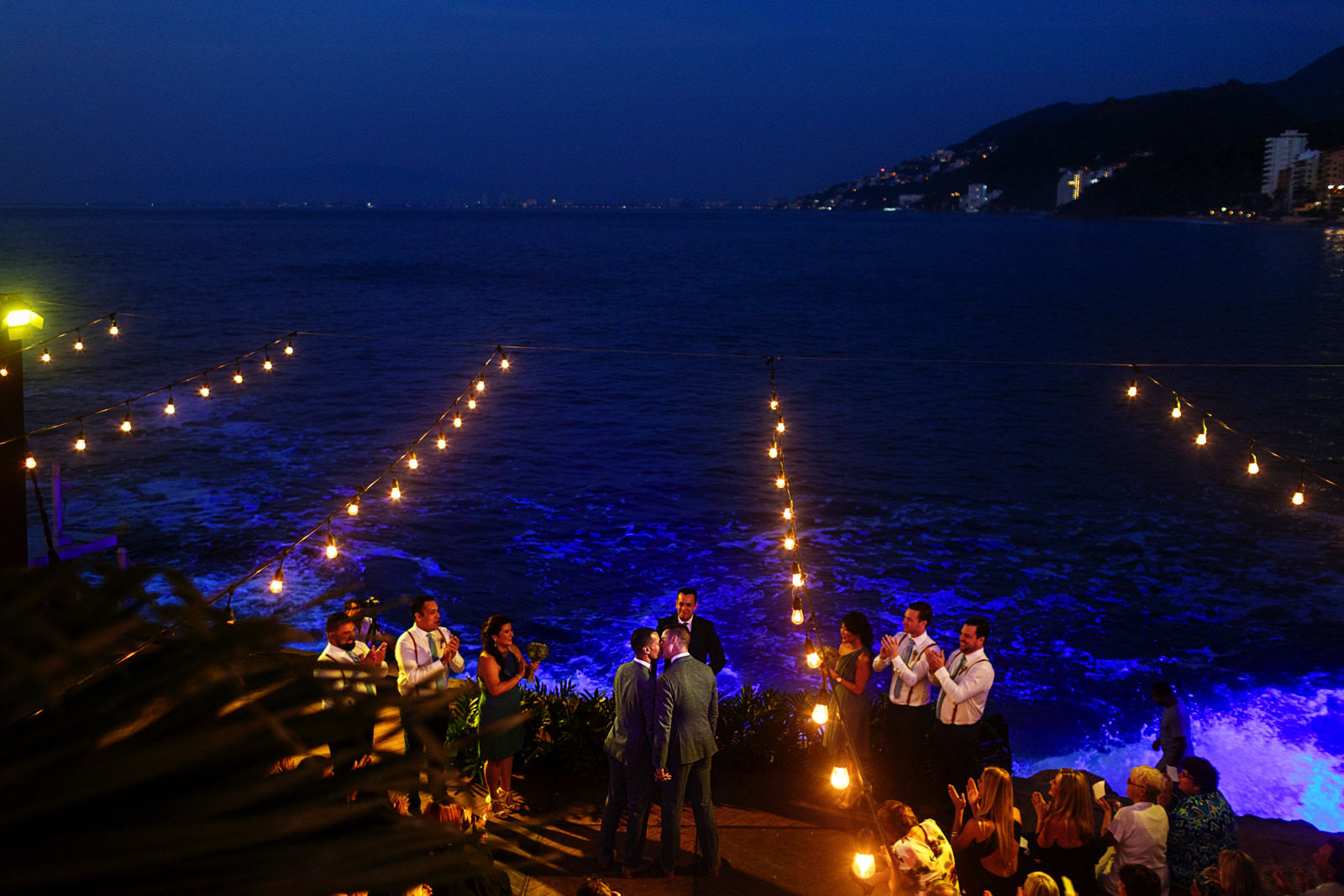 Grooms first kiss at the end of the gay wedding ceremony with a view of the ocean and mountains during the sunset