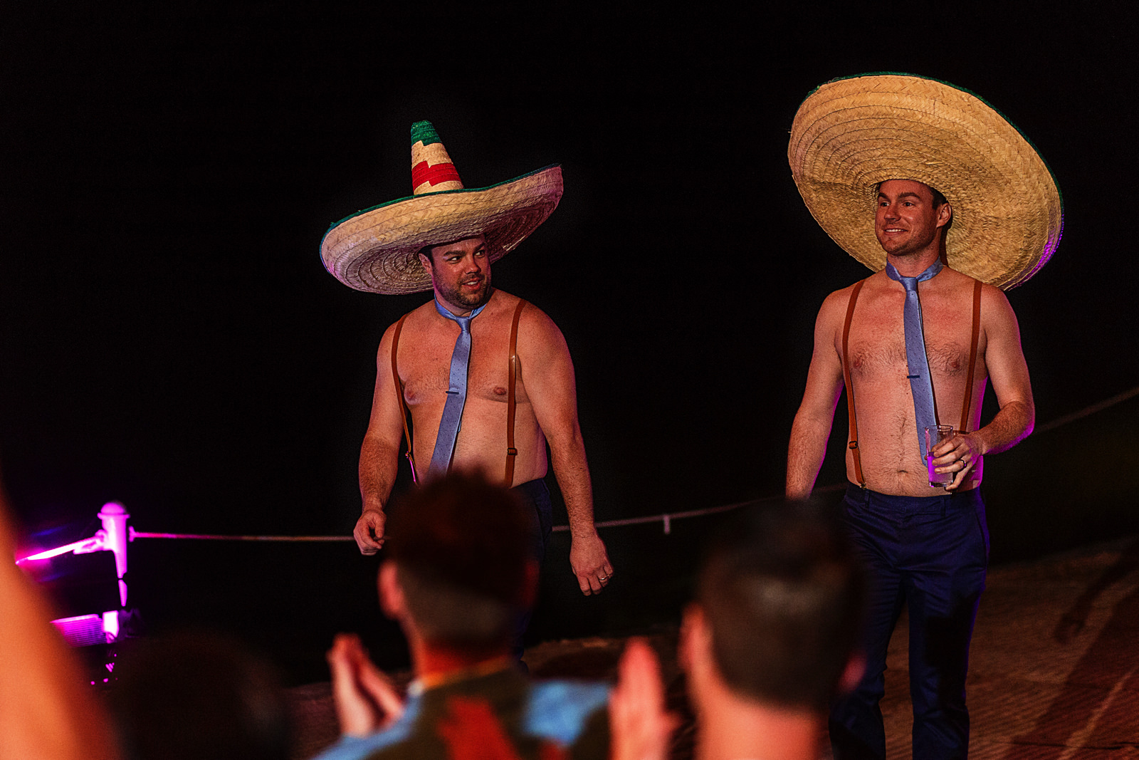 Groomsmen with no shirt entering into the dinner area with mexican sombreros