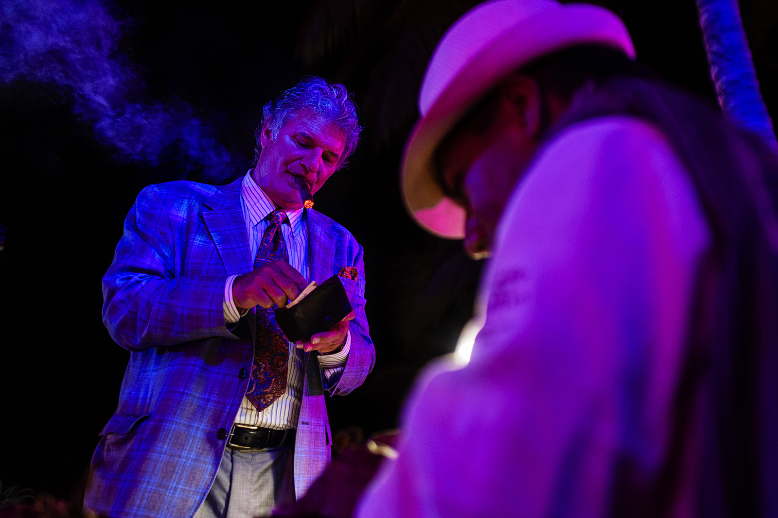 Wedding guest with a cigar in his mouth giving a tip to the cigar maker