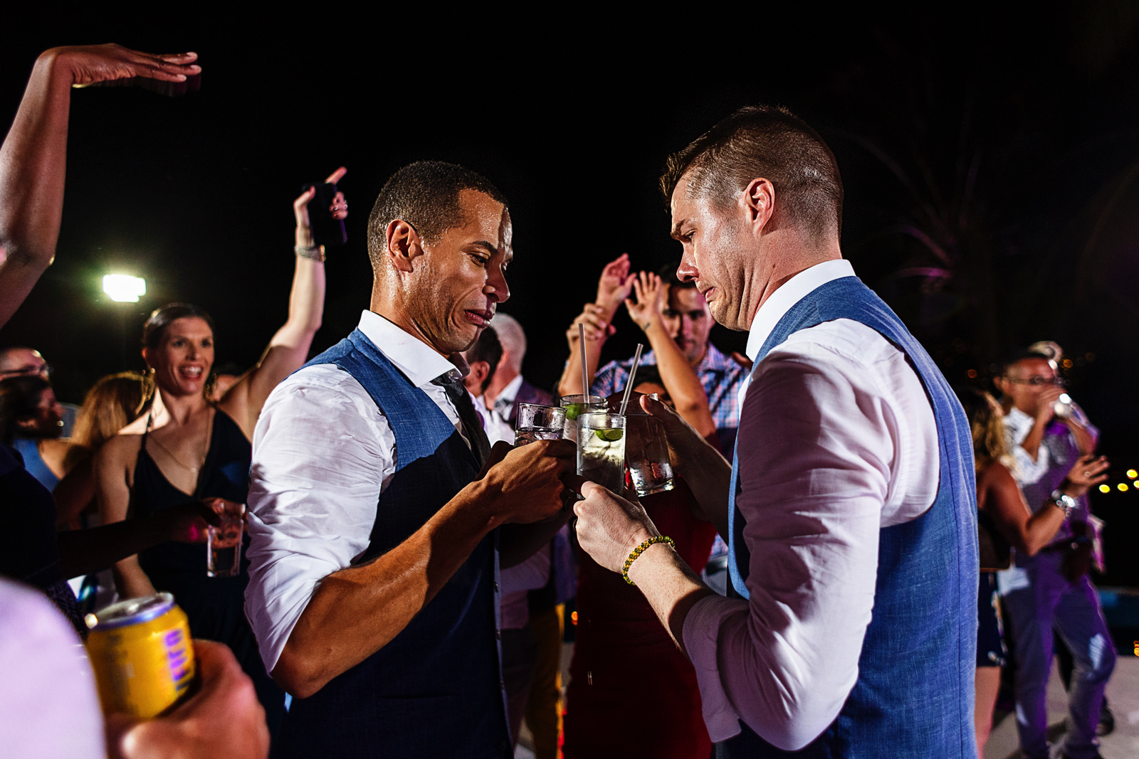 Grooms make funny faces as they put their drinks together in the dancefloor