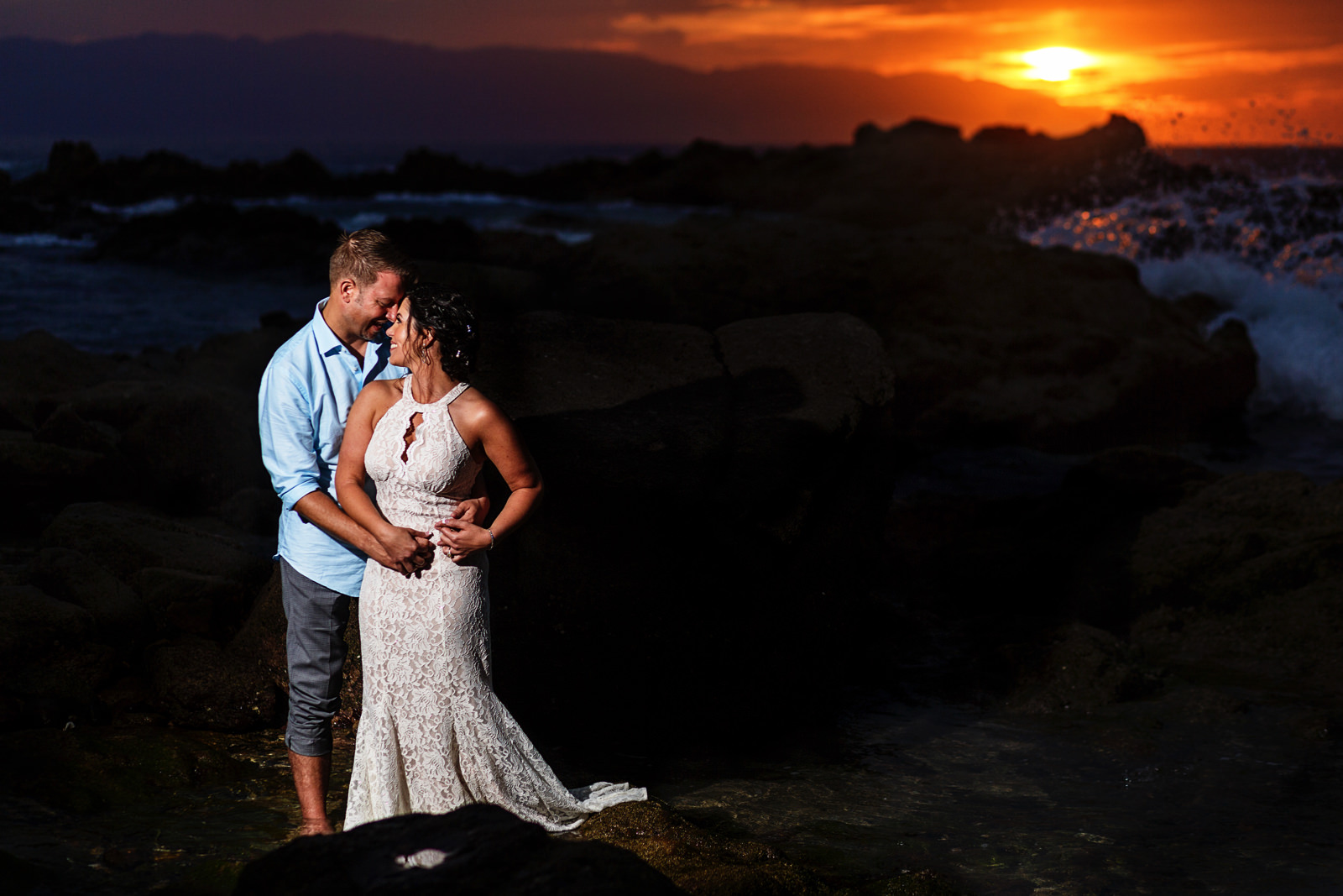Bride and groom standing on rock over the ocean near the beach with a sunset in the background