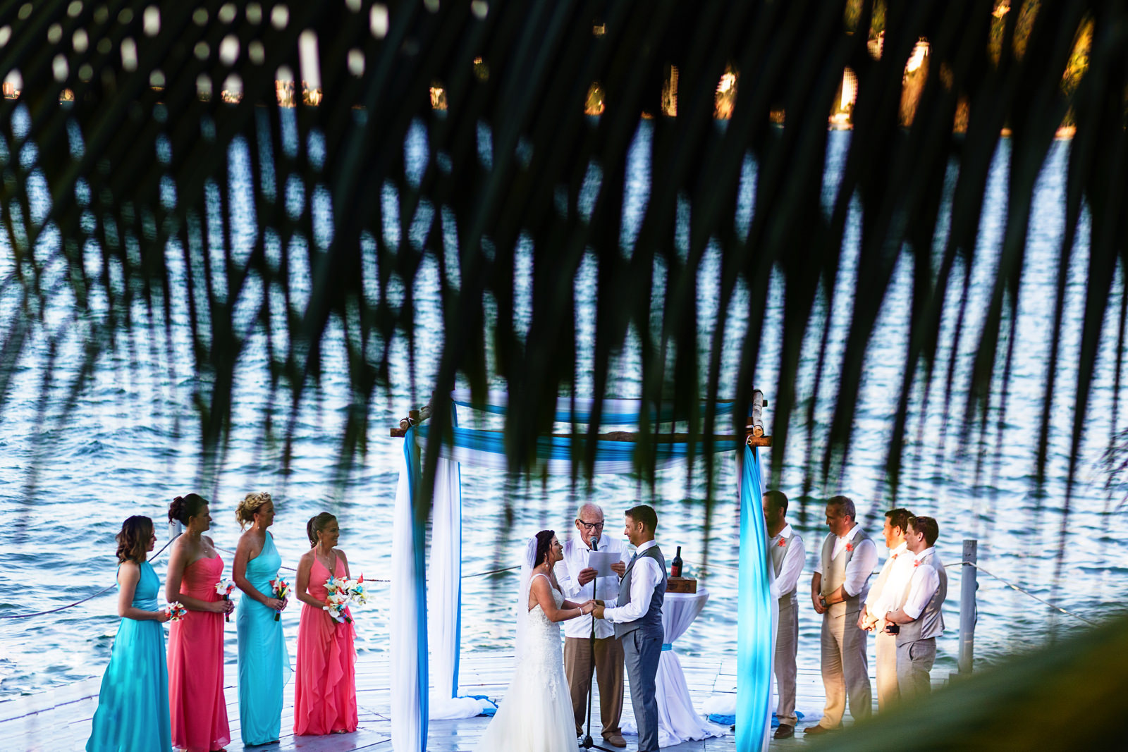 Destination wedding ceremony in progress near the ocean through a palm branch