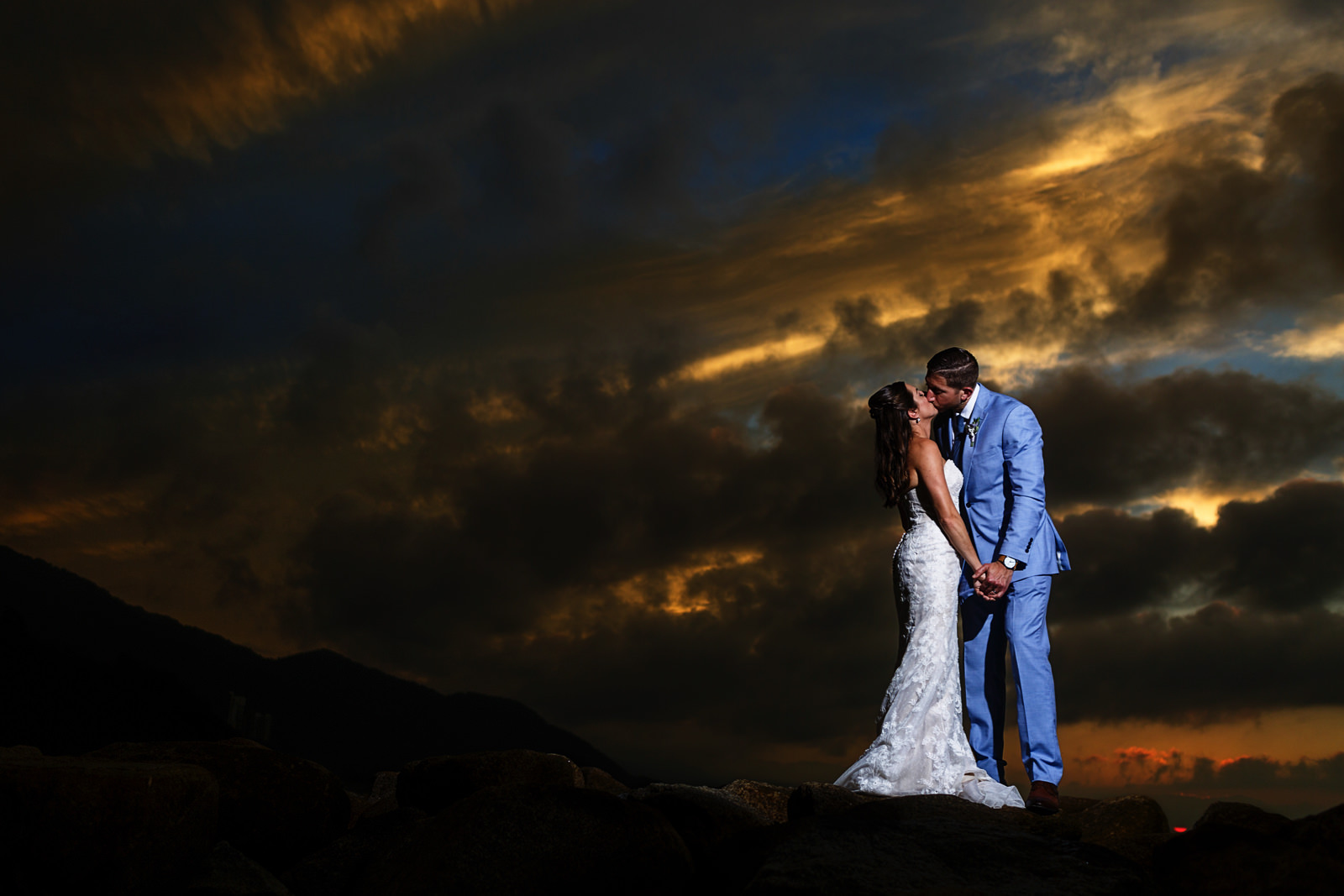 Groom and bride kissing under the beautiful sunset in Cabo San Lucas, Mexico.