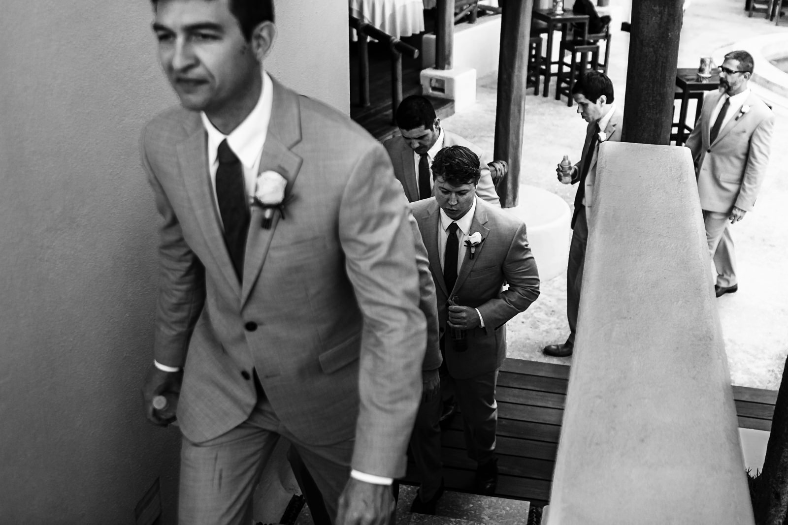 Groomsmen walking up the stairs towards the ceremony