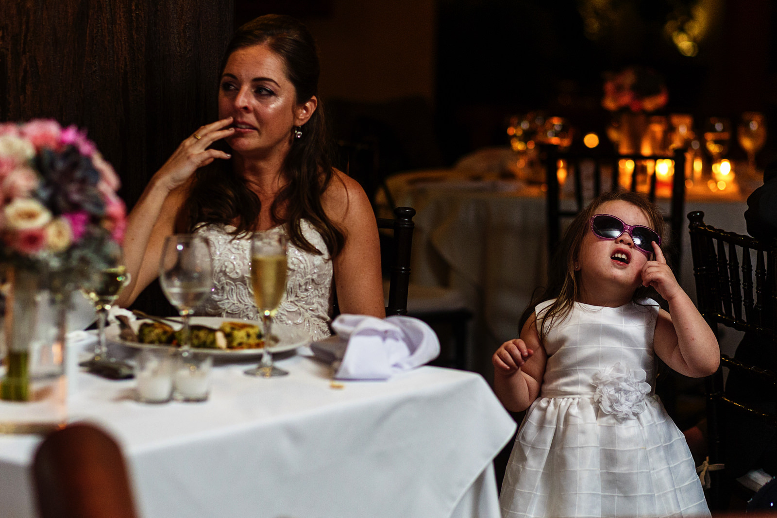 Little girl poses with sunglasses right next to the bride during the speeches