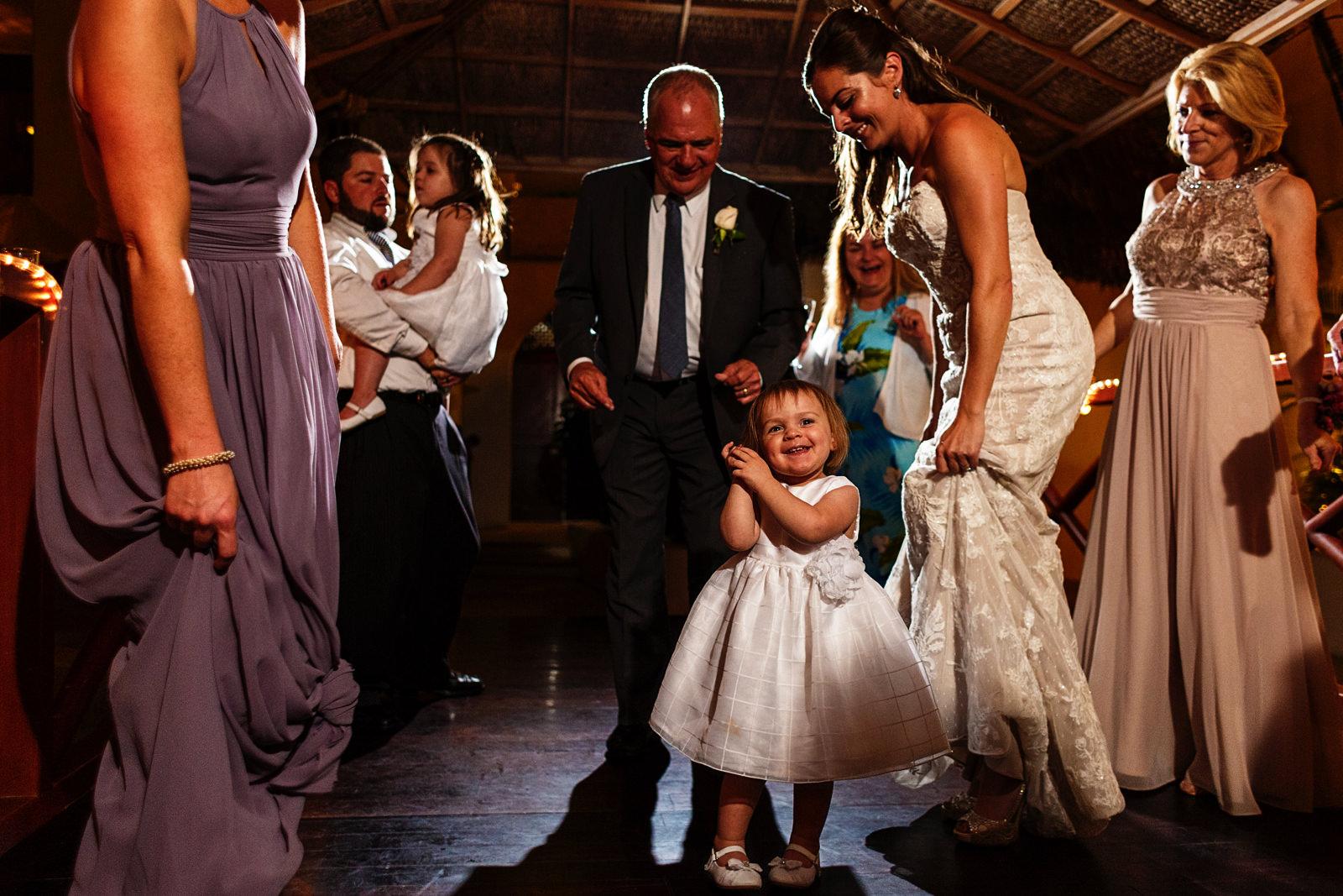Little girl dancing between bride and wedding guest