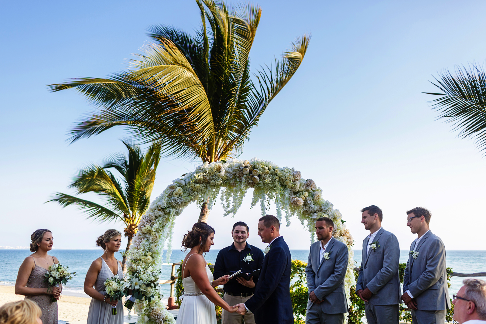 Bride reads her vows during the wedding ceremony with the ocean in the background