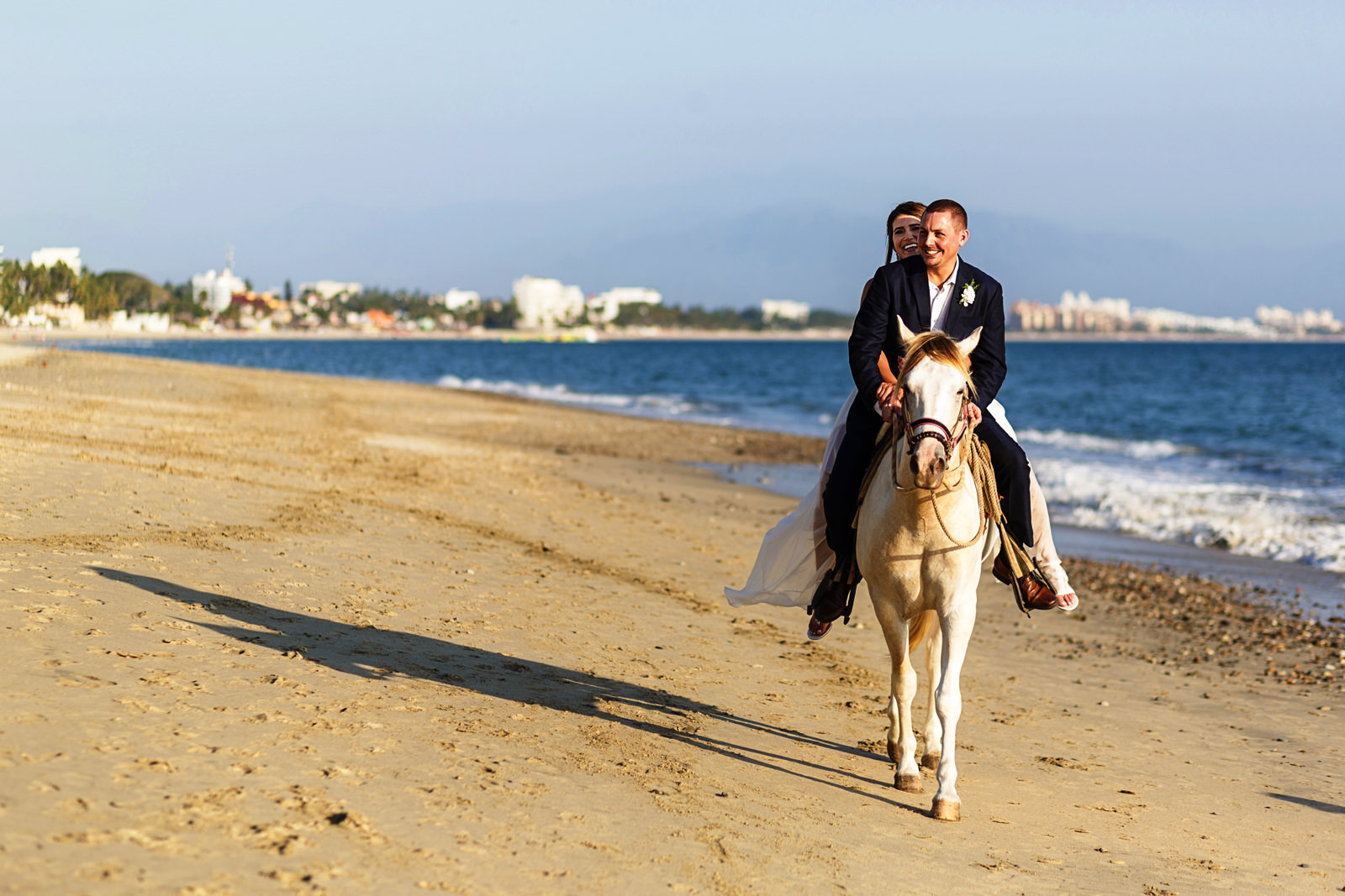 Bride and groom horse backridding on the beach