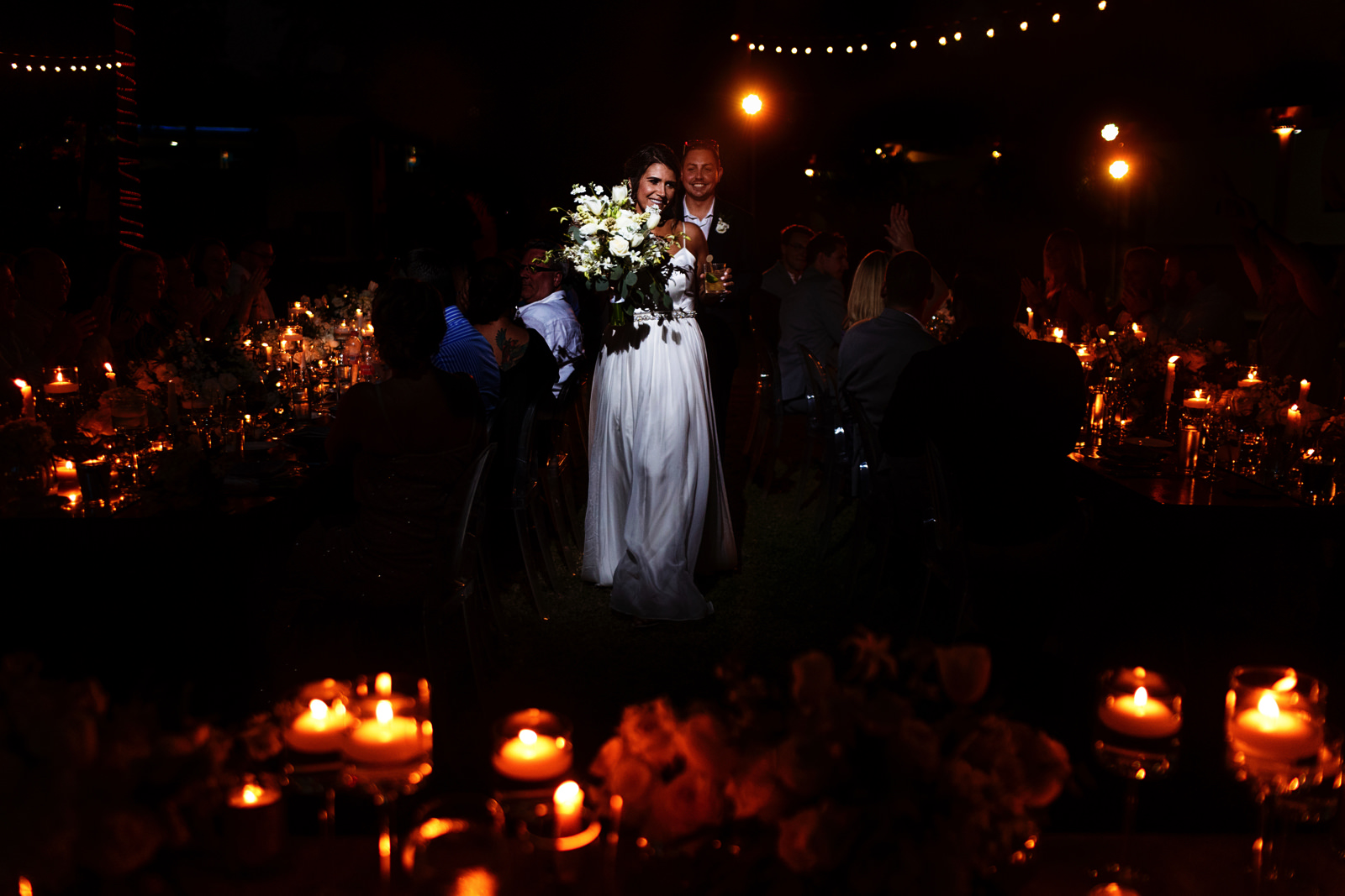 Bride and groom entrance into the reception between the dinning tables filled with candles