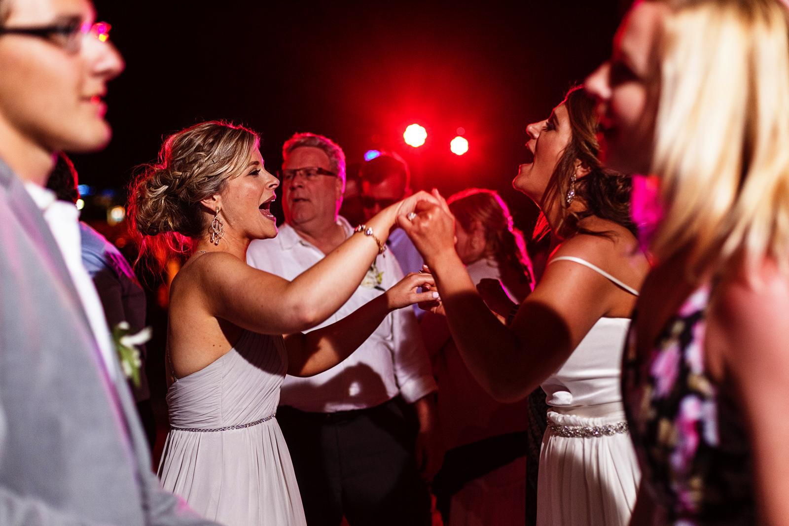 Bride and sister dancing and singing at the dancefloor