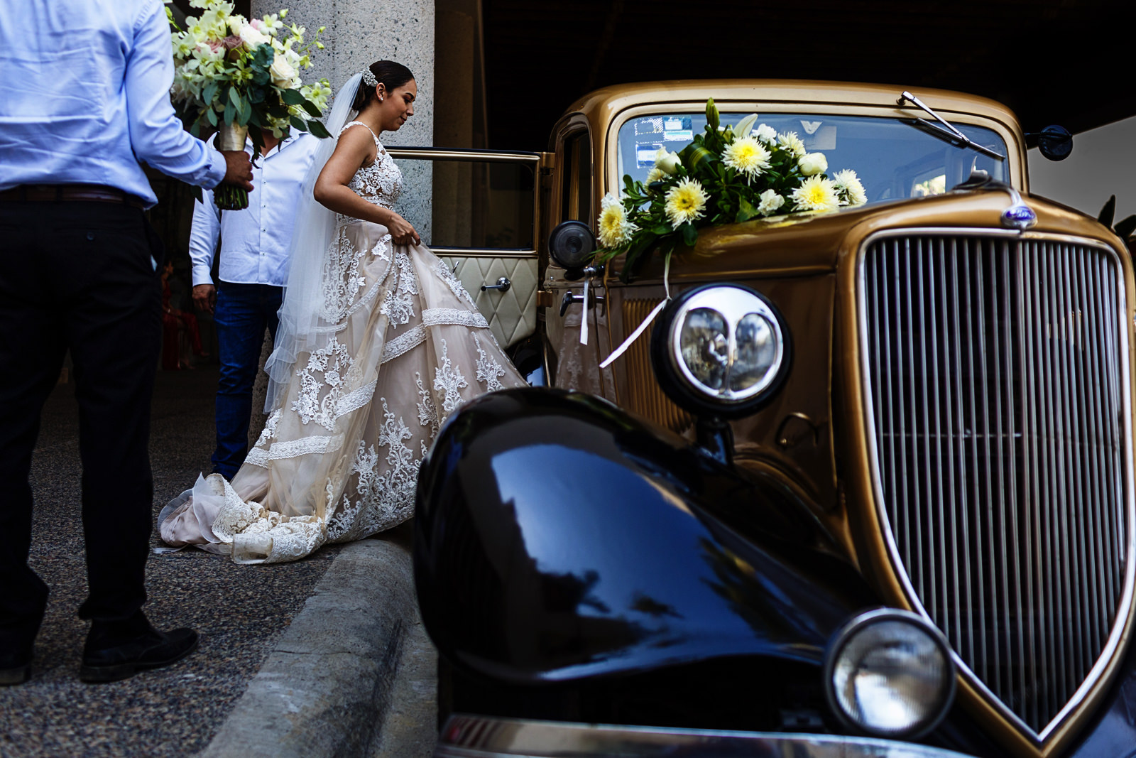 Bride getting into a classic car to go to her catholic wedding ceremony