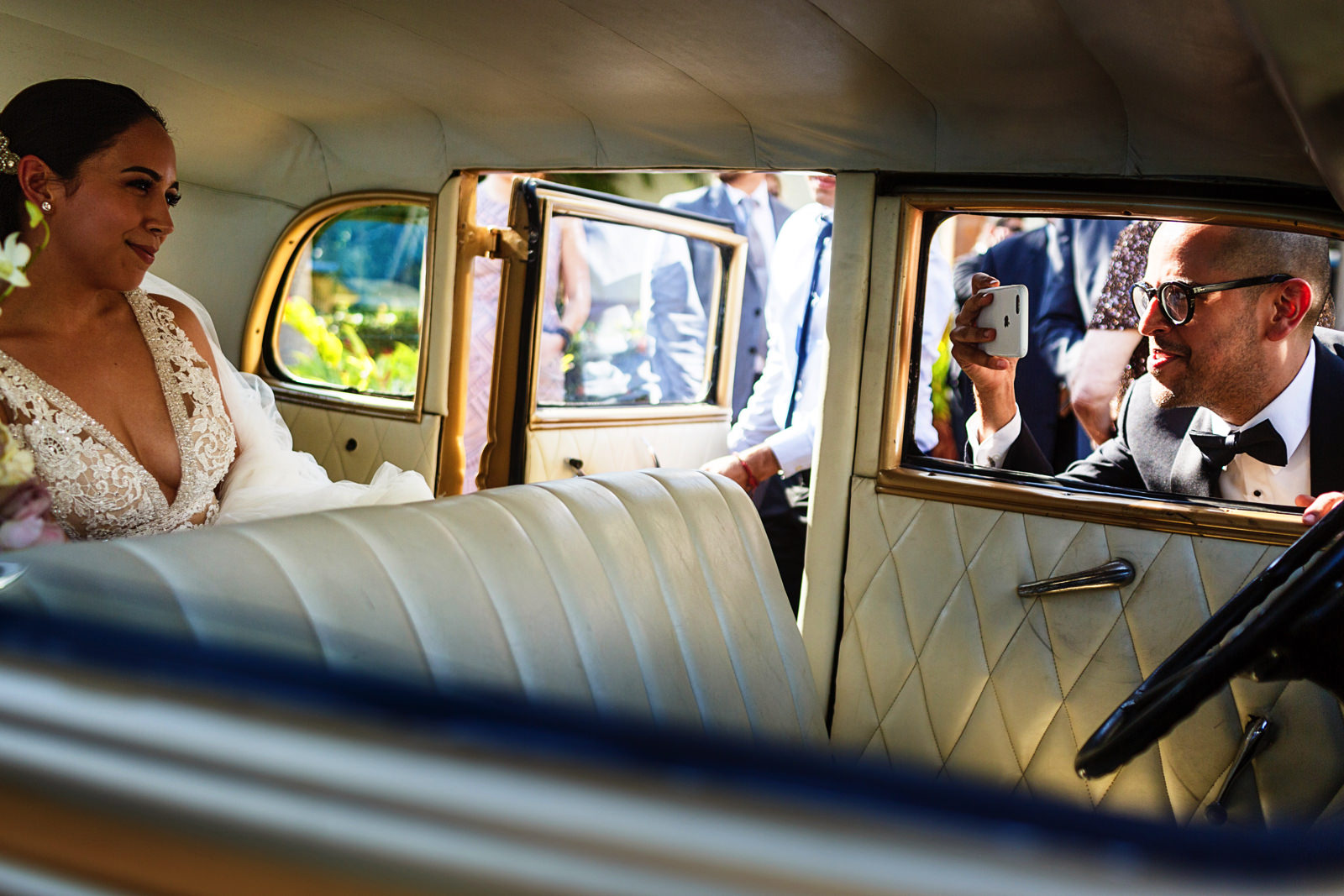 Brother-in-law snaps a photo of the bride inside the classic car after the wedding ceremony