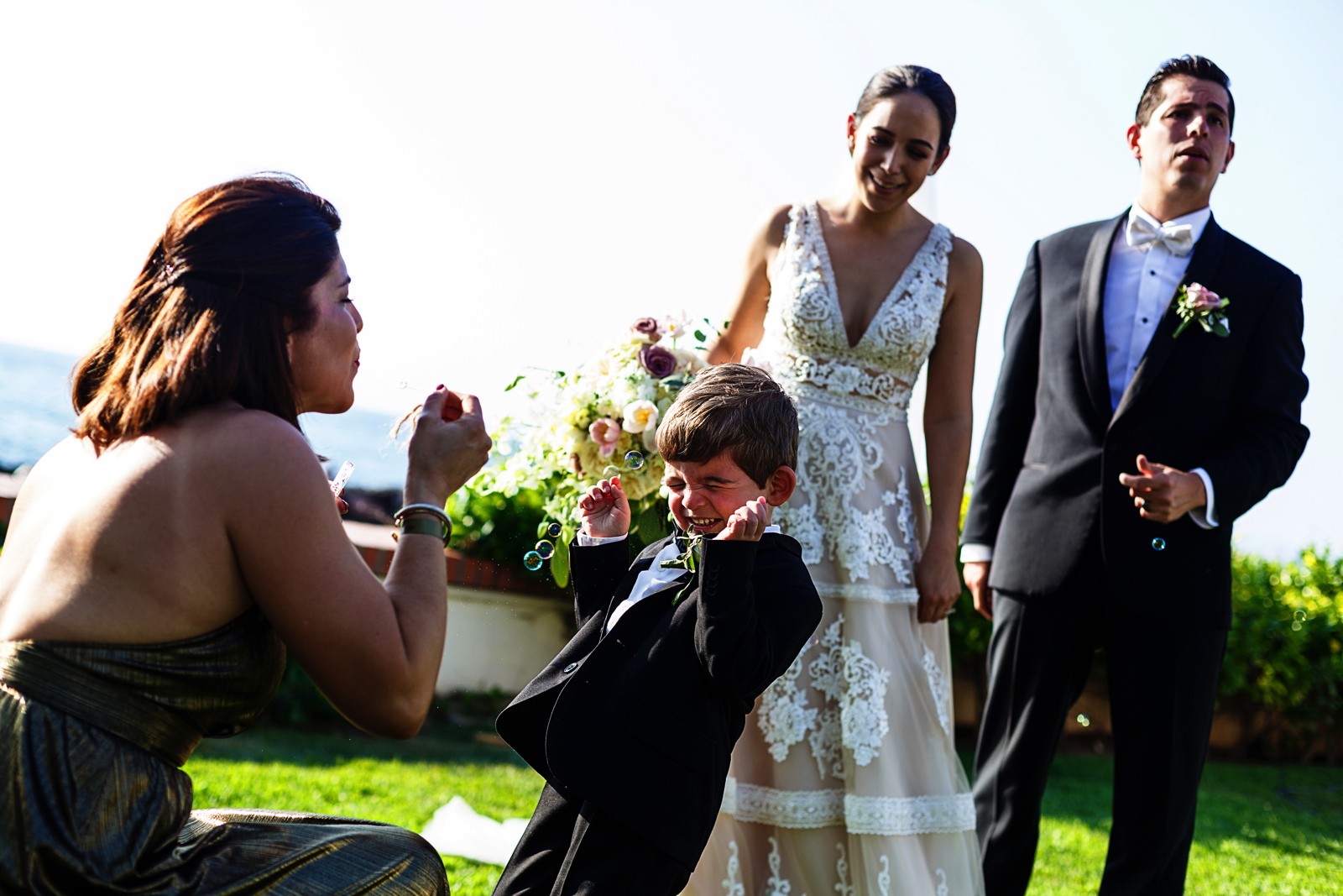 Kid reacts to bubbles being blowed at him in front of the groom and bride