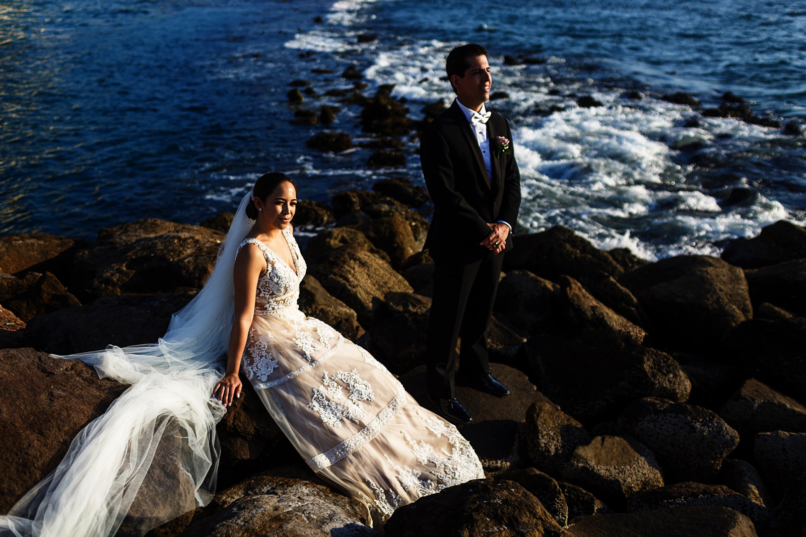 Portrait of bride and groom on the rocks with the ocean in the background