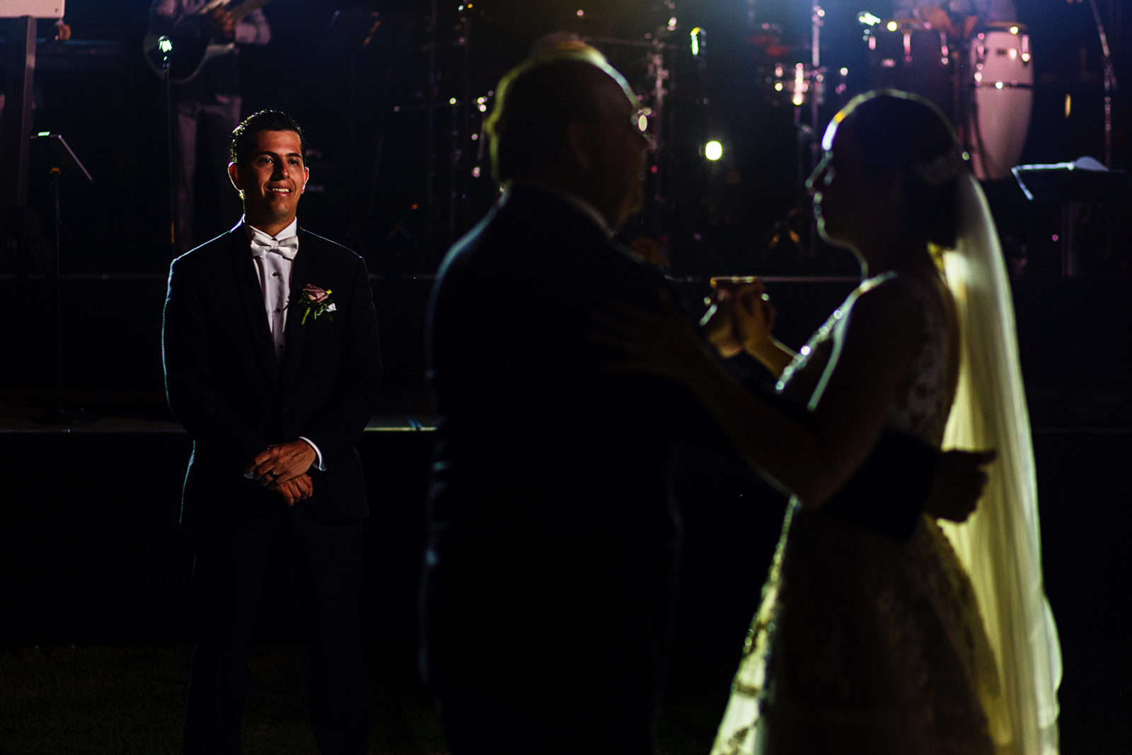 Groom smiling as he sees the father and bride dance