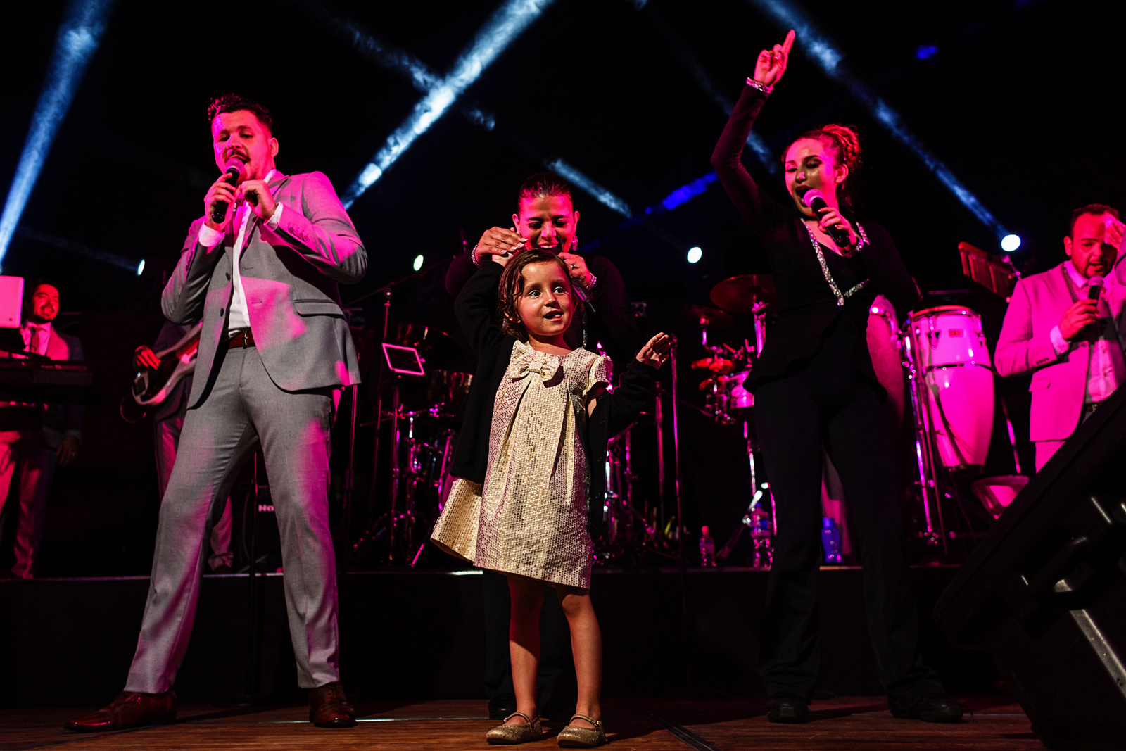 Little girl dances on stage with singers of the music band for the wedding