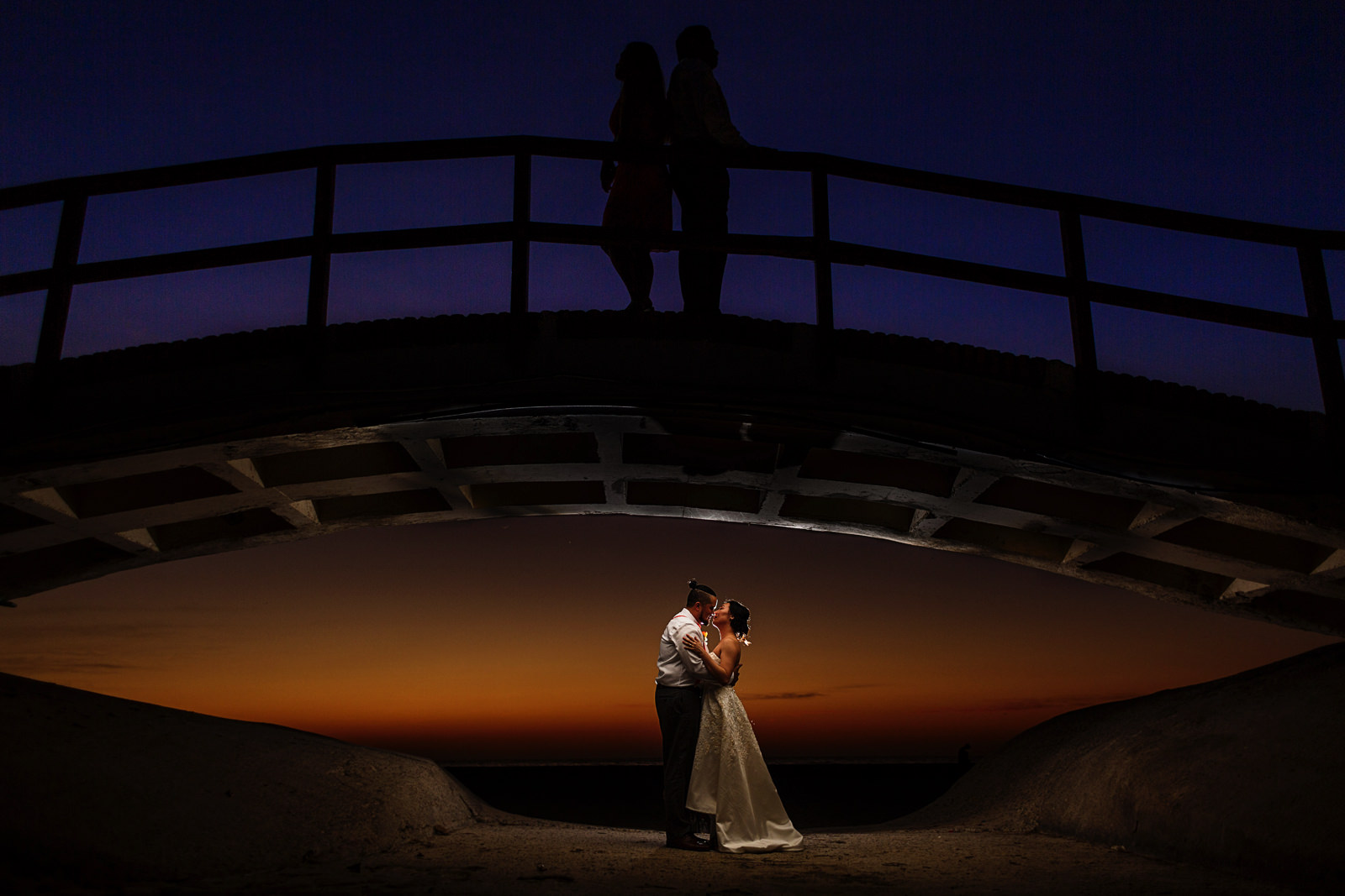 Bride and groom under a bridge with best man and matron of honor over the bridge with mexican sunset in the background.