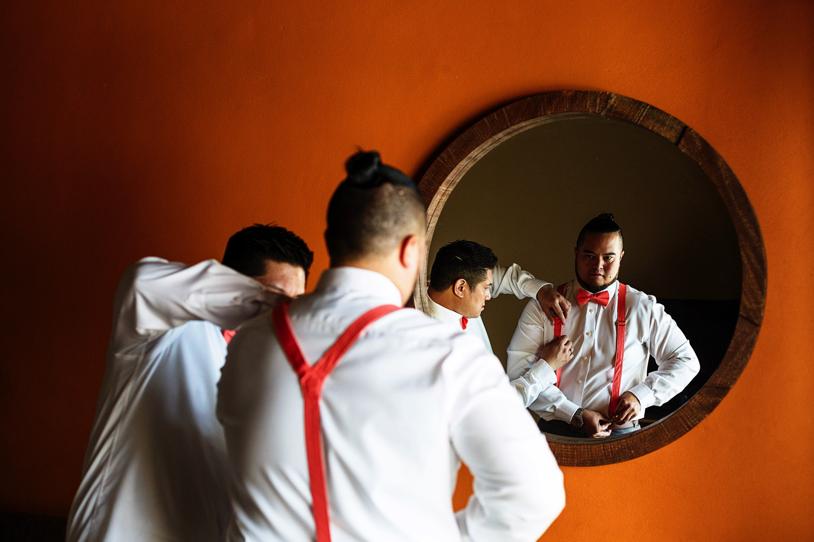 Groom getting his suspenders in front of a mirror on an orange wall