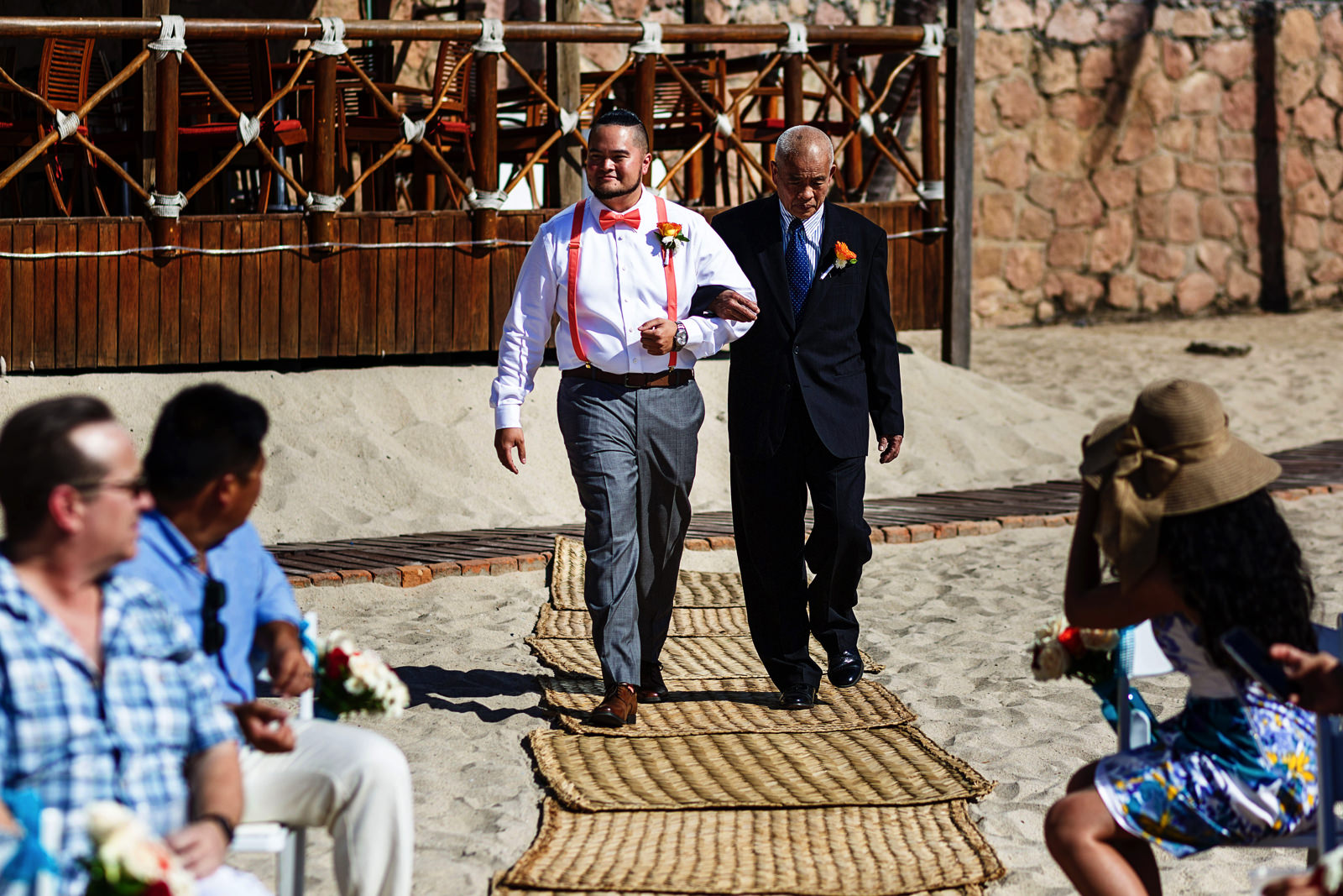 Groom walks down the aisle with the father of the bride on the beach