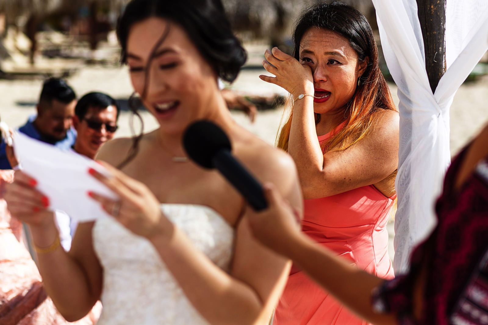 Maid-of-honor cries behind the bride while she is receiving her vows