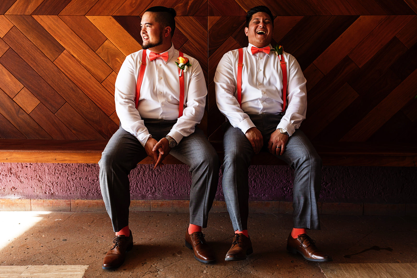 Groom and best man wearing matching outfits laugh sitting on a bench