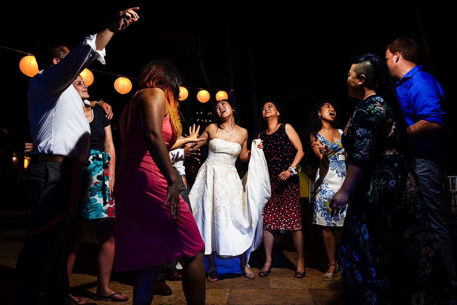 Bride and mom dance in group with other wedding guests