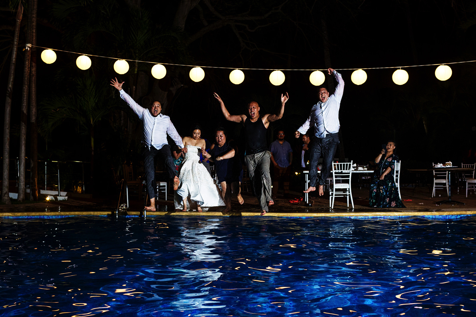 Groom and bride jump into the hotel pool among other wedding guests