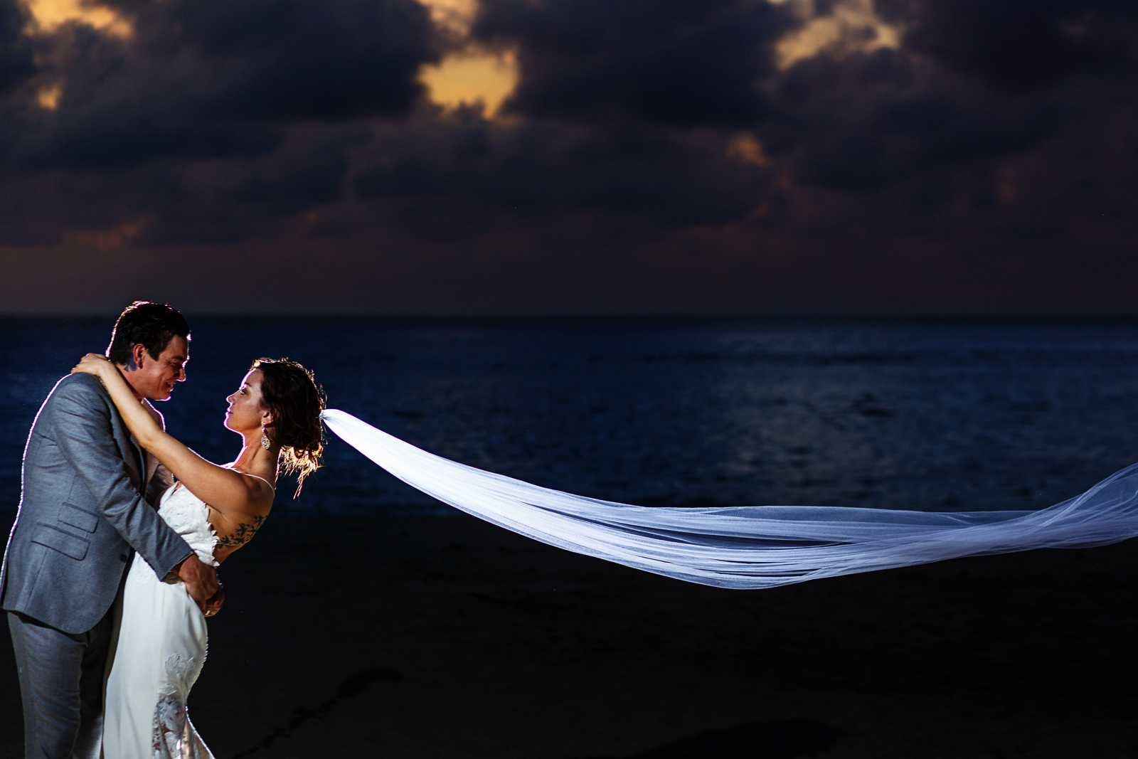 Bride and groom standing on the beach with the sunset in the background and the bride's veil floating in the air.